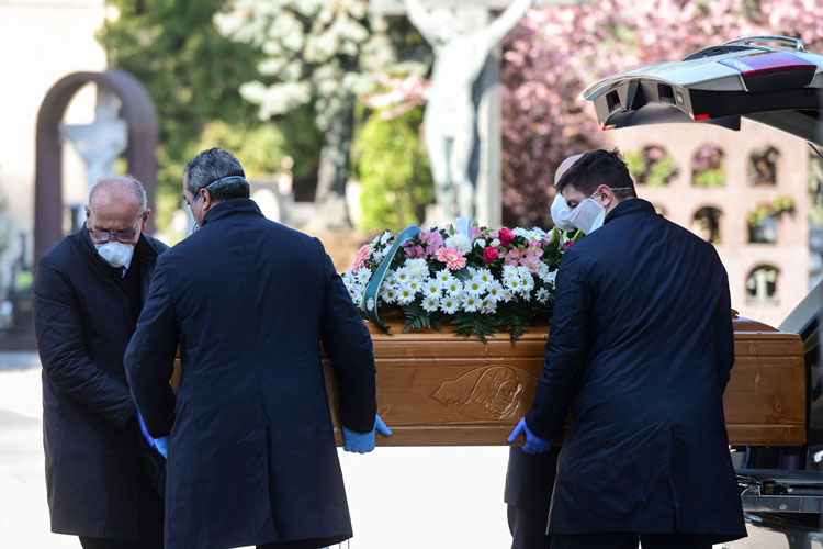 Undertakers wearing face masks unload a coffin out of a hearse on March 16 at the Monumental cemetery of Bergamo, Lombardy, as burials of people who died of the coronavirus are being conducted every half hour.