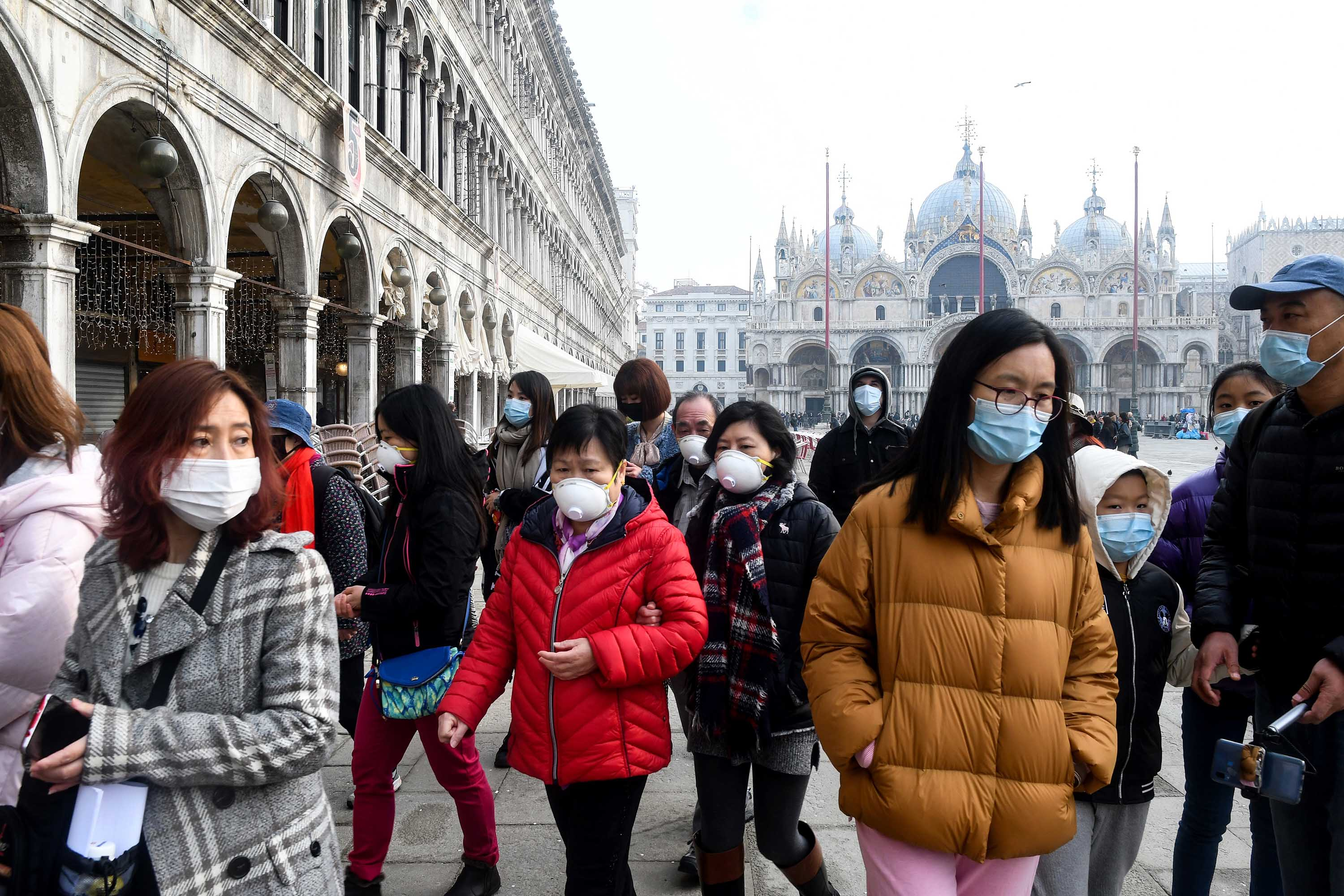 Tourists wearing protective face masks visit the Piazza San Marco in Venice, Italy on Monday.