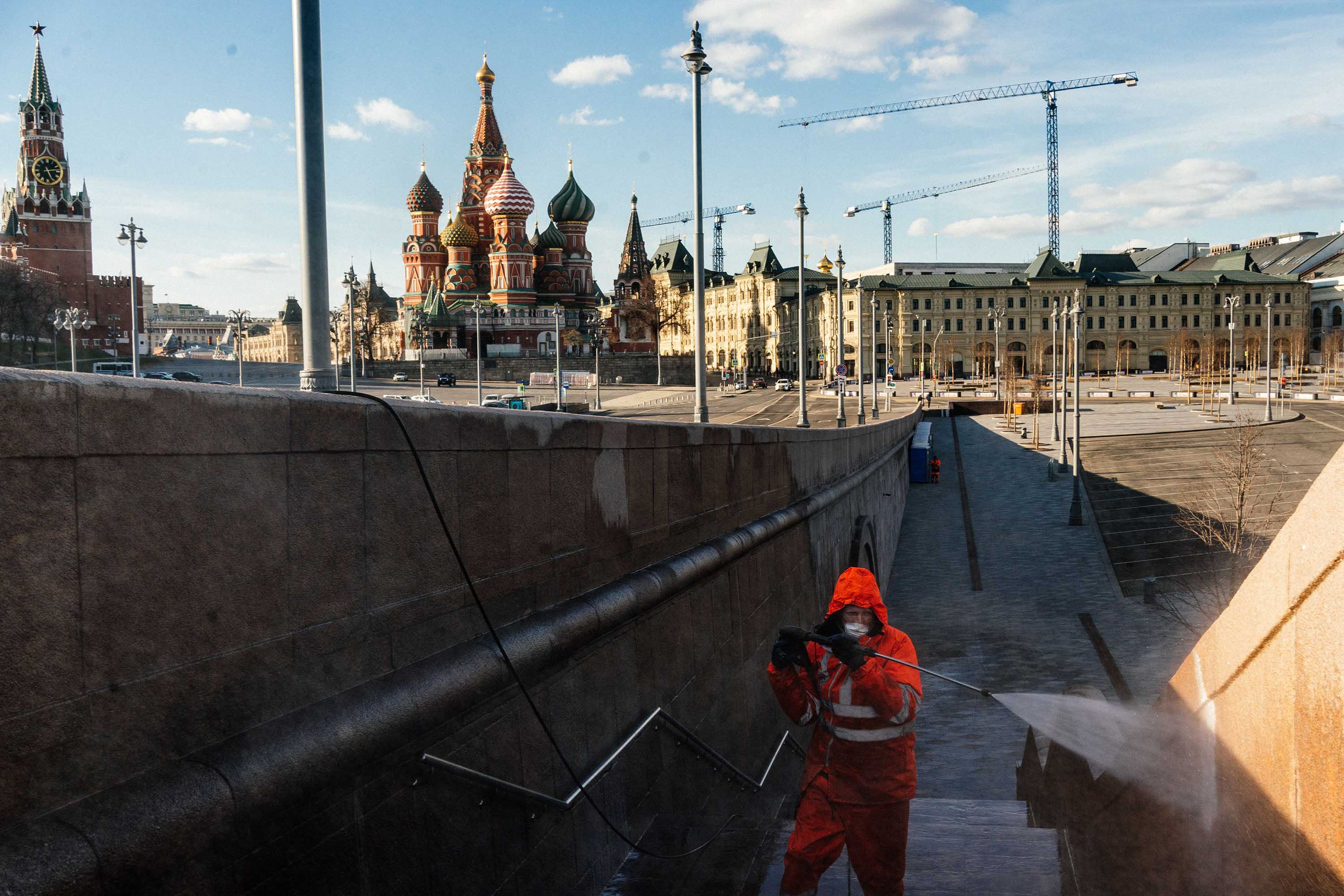A municipal worker disinfects a bridge near the Kremlin in Moscow on April 12.