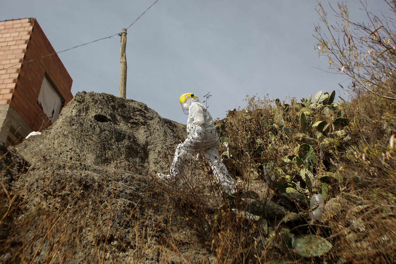 A health worker wearing a face mask and a suit walks in a difficult access road during an operation to identify Covid-19 cases on July 7 in La Paz.