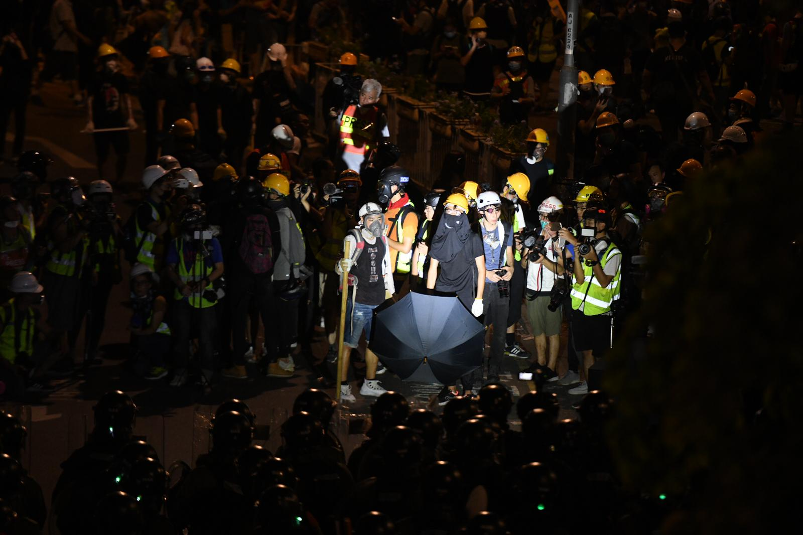 Police shine a spotlight on a small group of remaining protesters in Yuen Long.