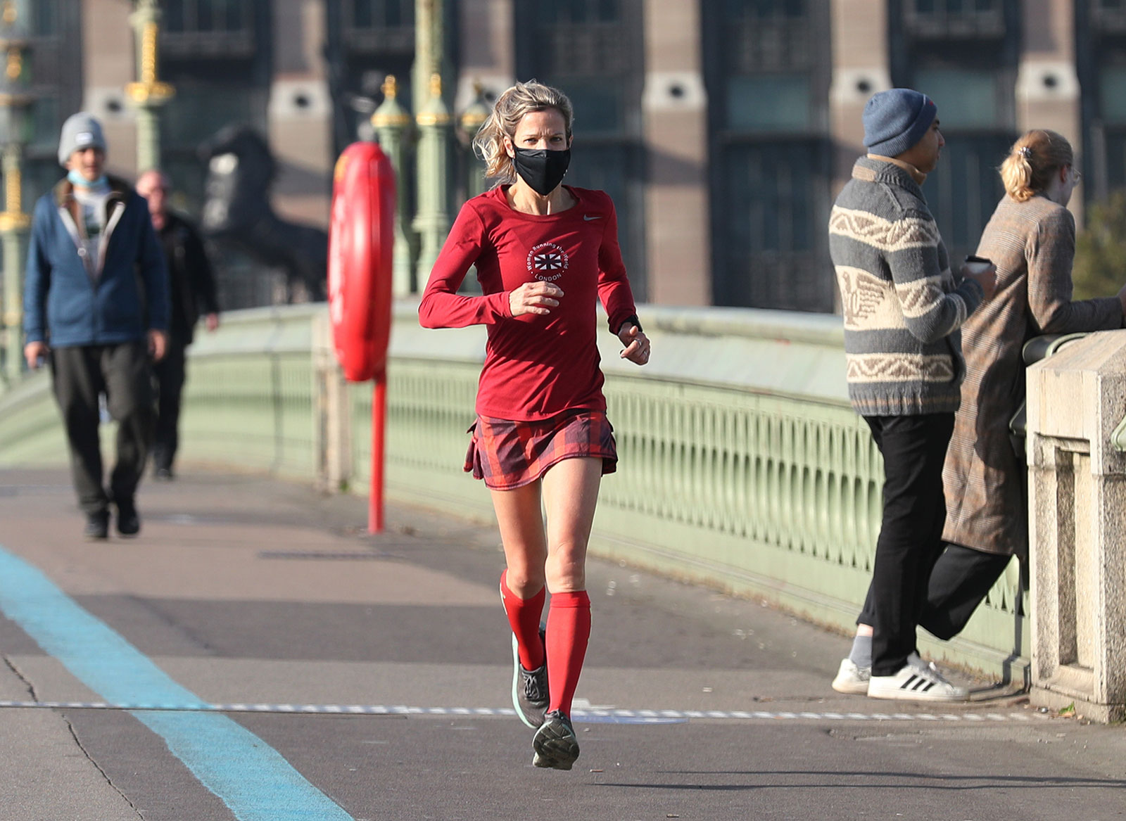 A woman wearing a face mask runs across the Westminster Bridge in London.
