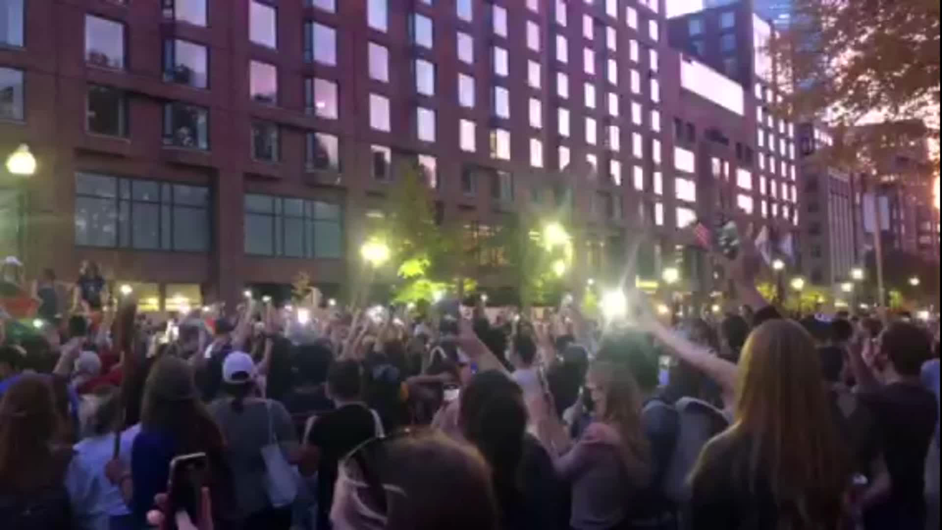 "A crowd sings ""We Are the Champions"" on Saturday in Boston, Massachusetts."