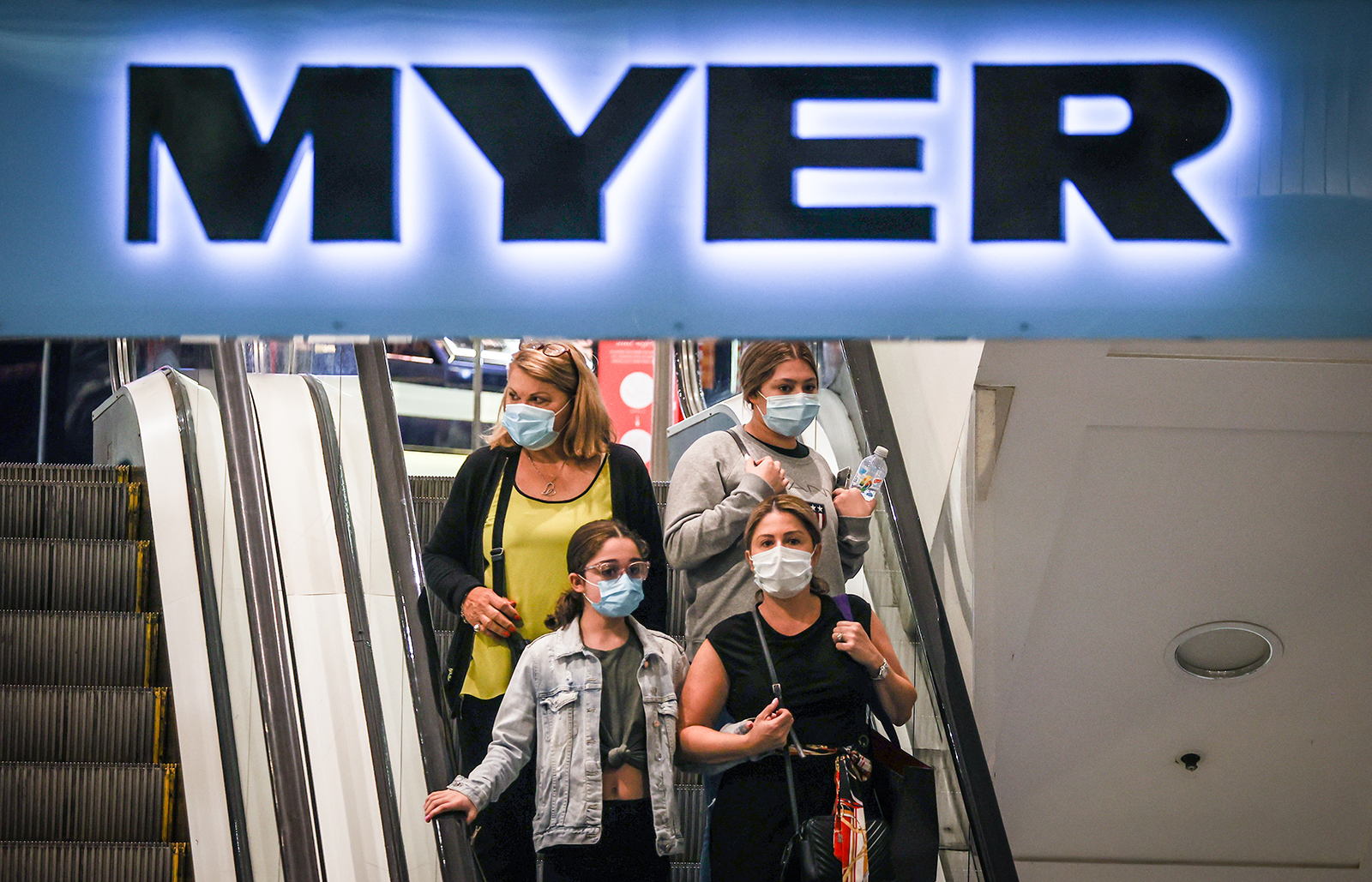 Shoppers wearing face masks ride an escalator as they exit the Myer store located in the Pitt Street Mall in Sydney, Australia, on December 26, 2020.