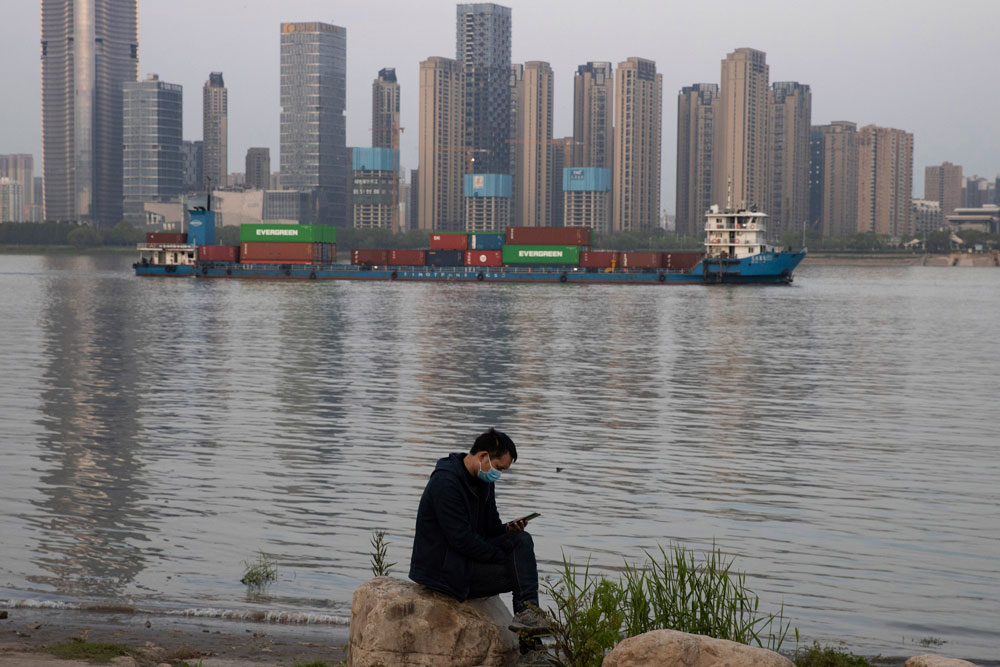 A man wearing a mask checks his phone as a container ship cruises along the Yangtze River in Wuhan in China's Hubei province on April 13.