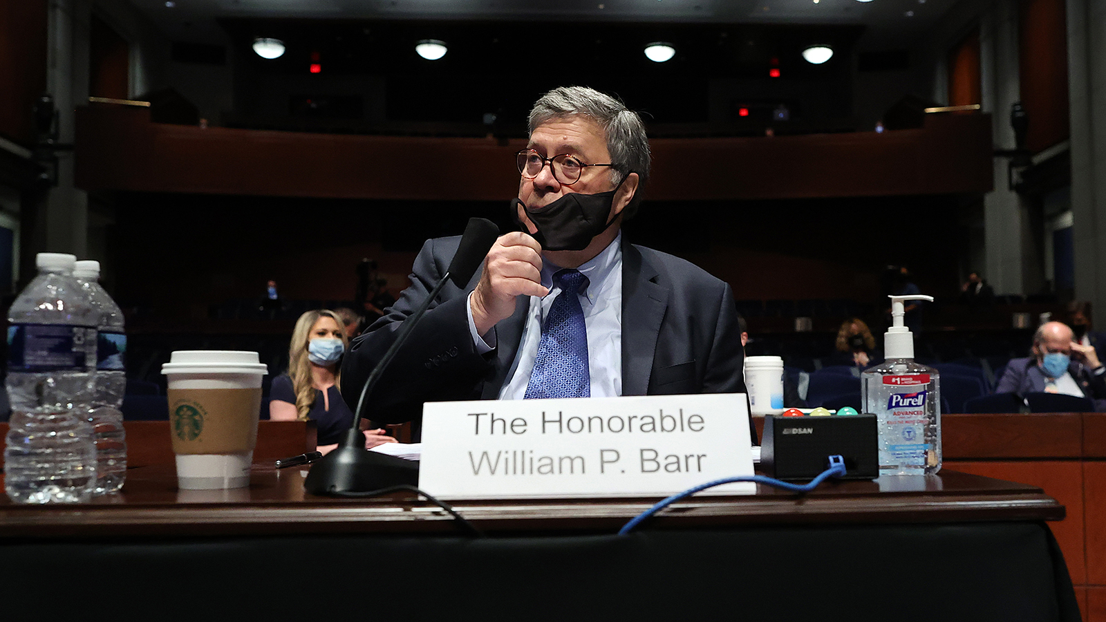 Attorney General William Barr removes his mask after a break in a House Judiciary Committee hearing on Capitol Hill on July 28 in Washington.