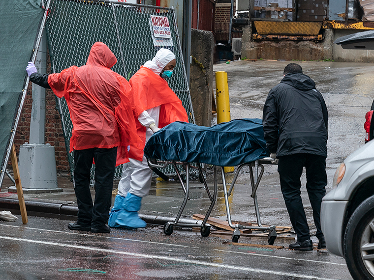 Funeral workers and hospital staff retrieve deceased bodies for burial at the Brooklyn Hospital Center on Monday, April 13, in New York.