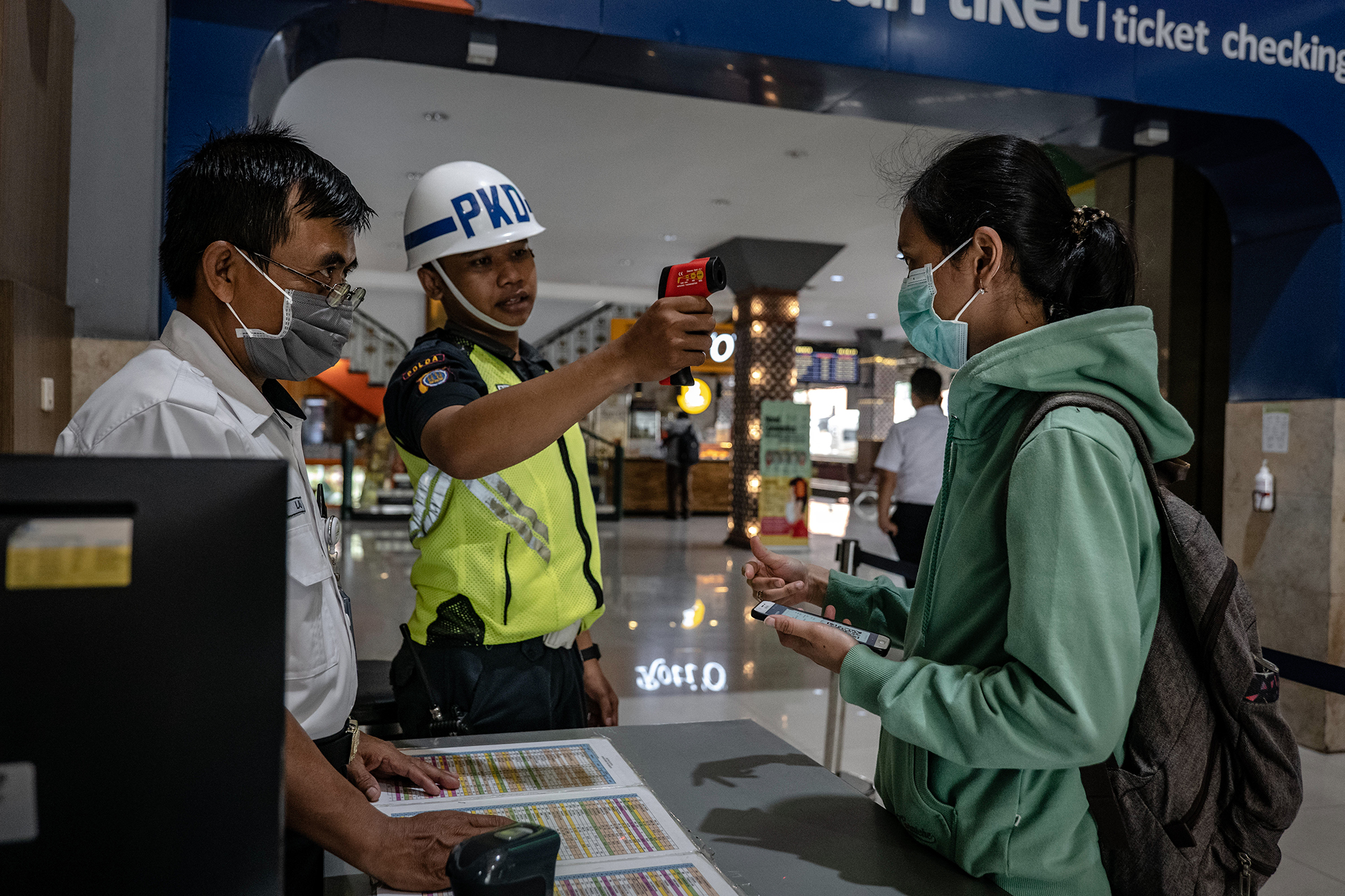 A security guard checks a passenger's body temperature at Tugu train station on March 12, in Yogyakarta, Indonesia.