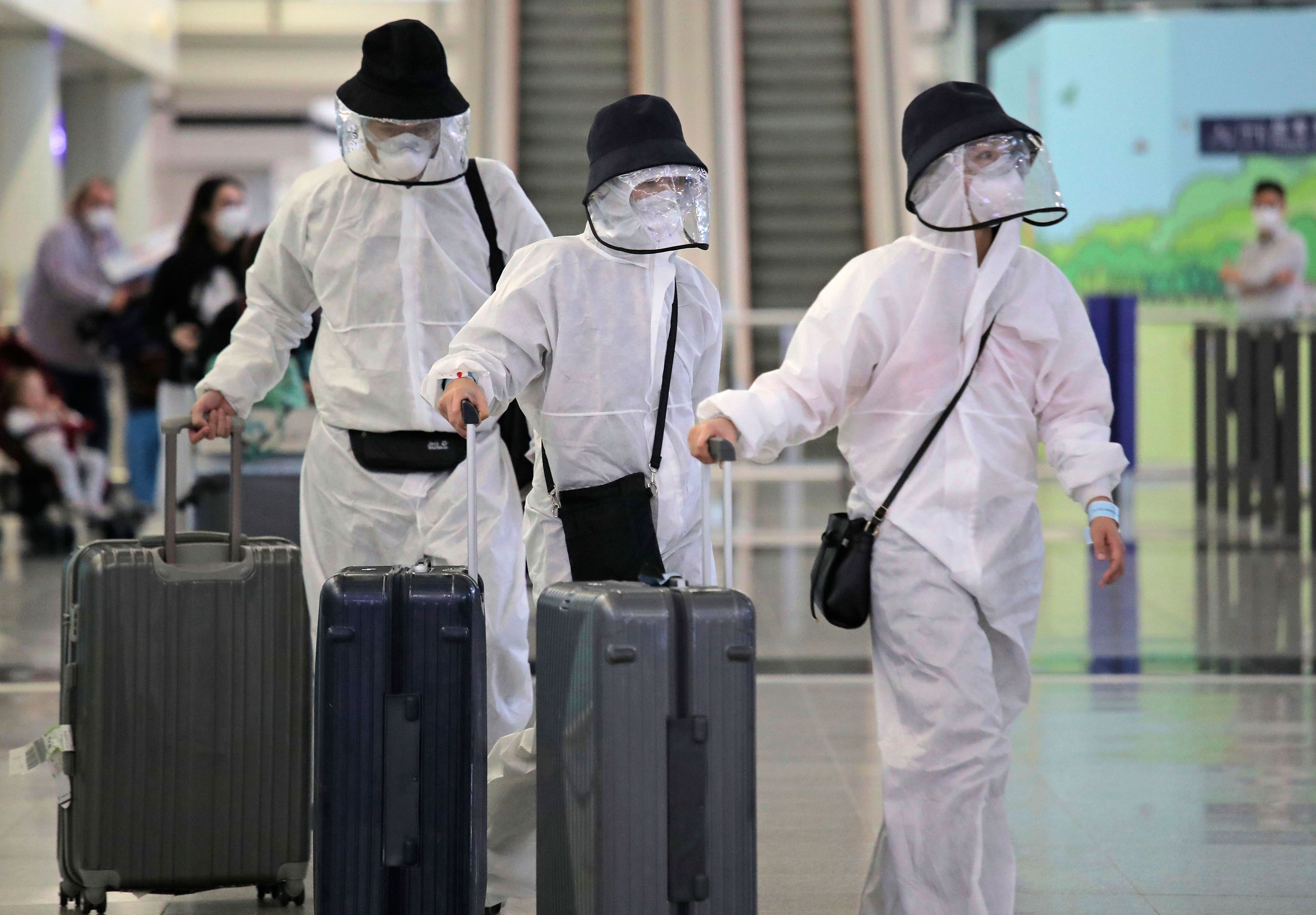 Passengers wear protective suits and face masks as they arrive at Hong Kong airport, Monday, March 23, 2020.
