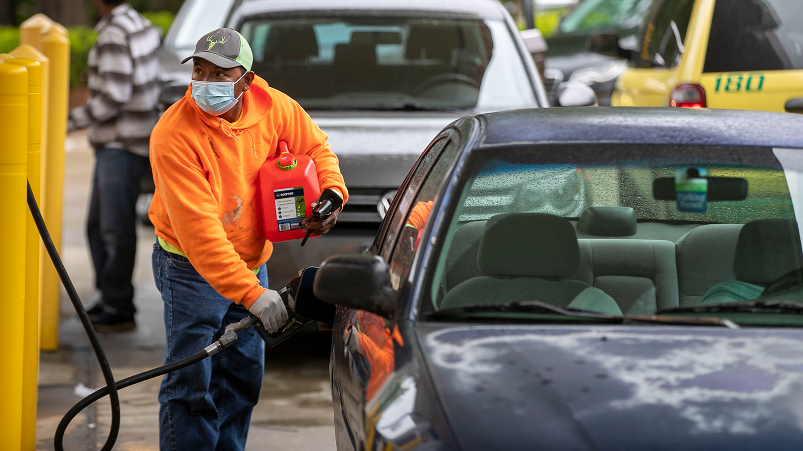 A customer fills up his car and gas container with fuel at the Circle K in Raleigh, North Carolina, on Wednesday.