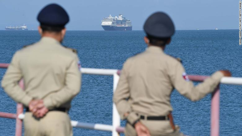 The Westerdam cruise ship is seen past Cambodian policemen as it approaches port in Sihanoukville, Cambodia's southern coast, on February 13.