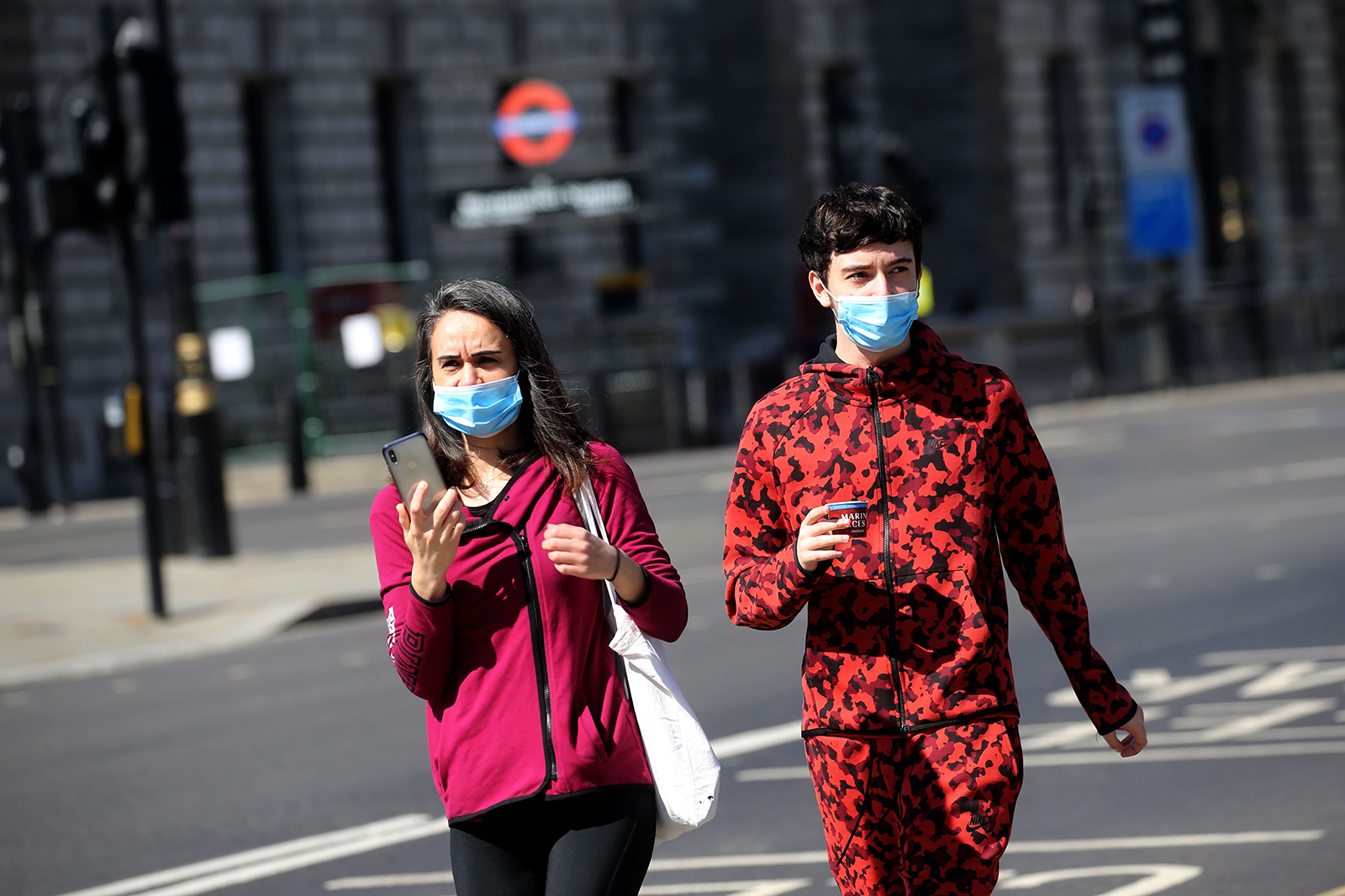 A couple wear face masks as they walk in central London on April 21.