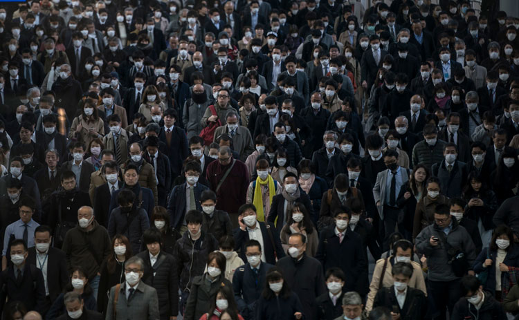 Commuters wearing face masks make their way to work on March 26 in Tokyo, Japan.