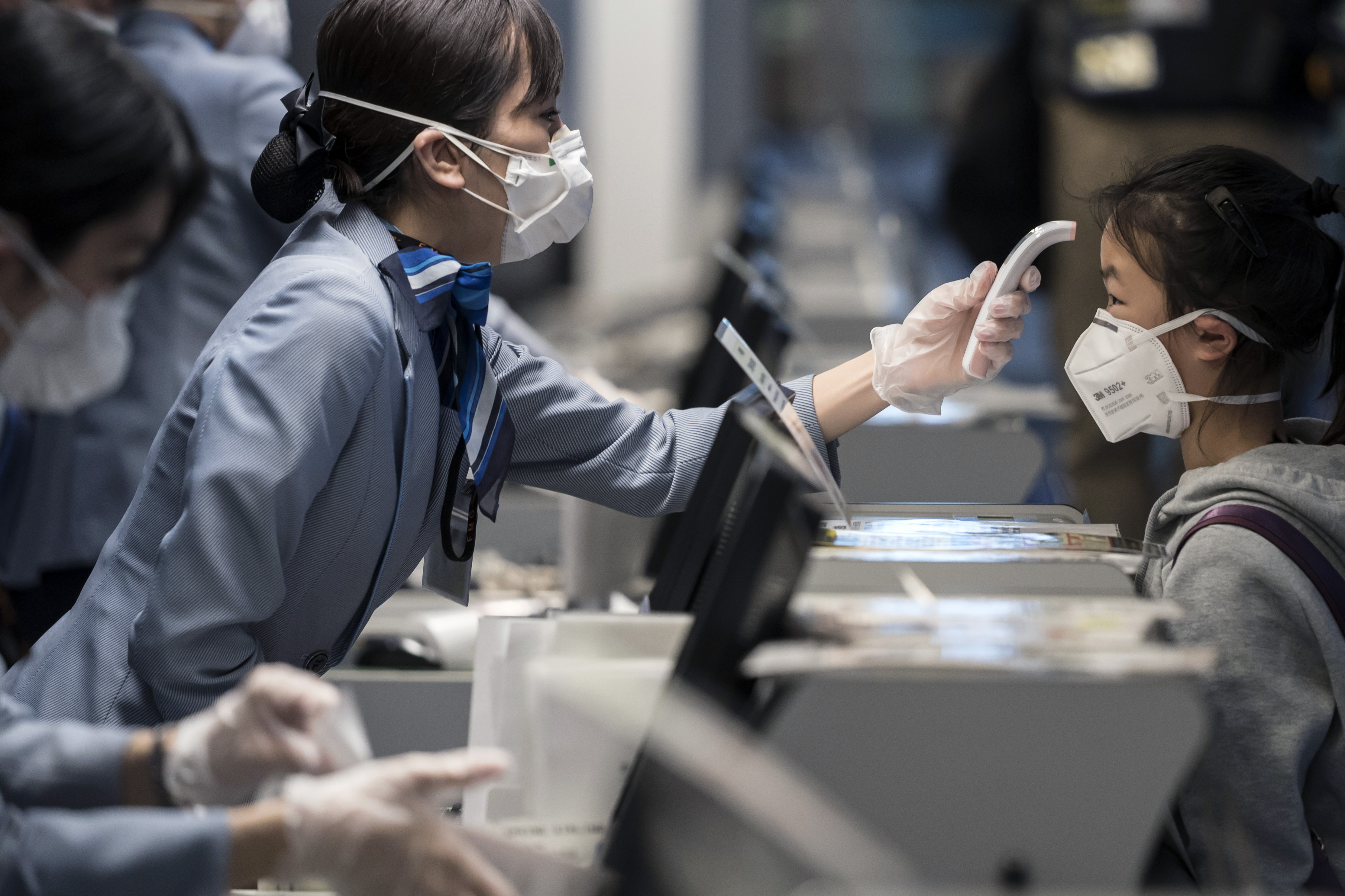 A passenger receives a temperature check at Haneda airport on January 31, 2020 in Tokyo, Japan.