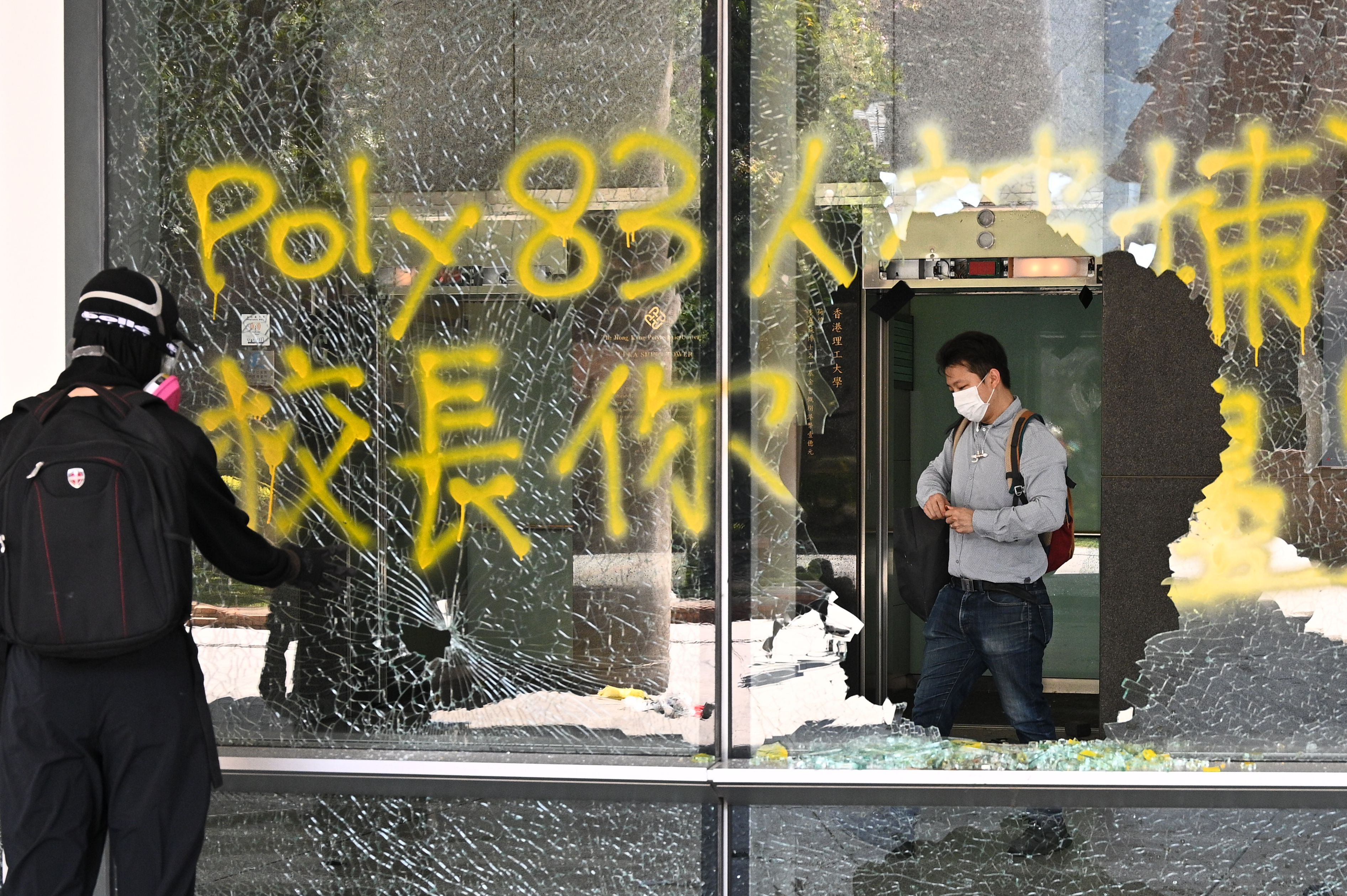 A man (R) stands inside a building as the windows were smashed up in the campus of the Hong Kong Polytechnic University.