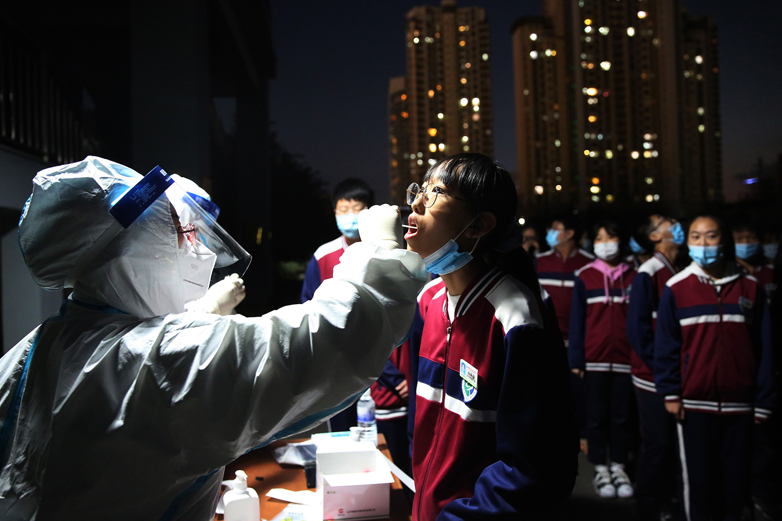 A health worker takes a swab from a middle school student to be tested for Covid-19, as part of a mass testing program following a new coronavirus outbreak in Qingdao, in China's eastern Shandong province, on October 12.