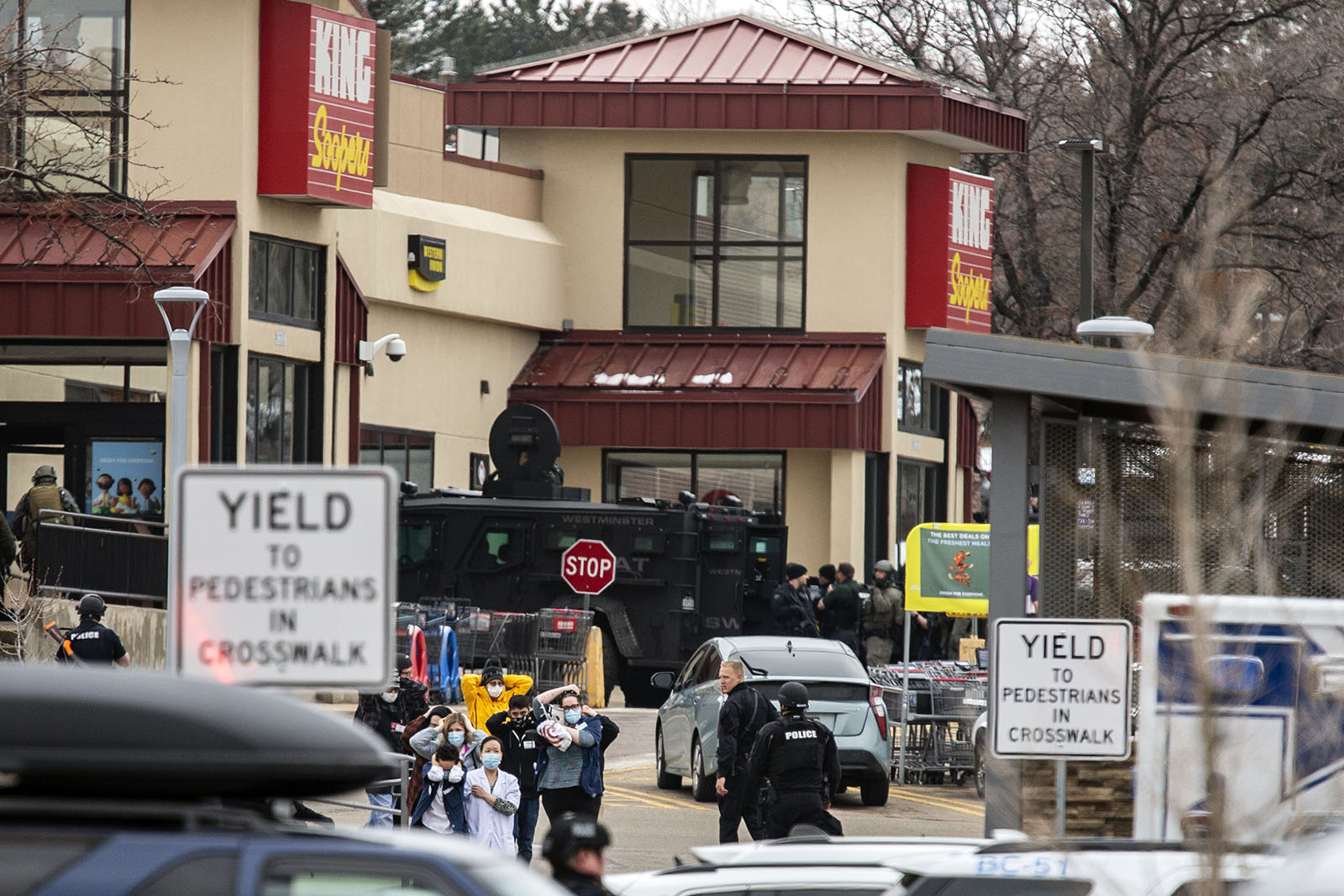 Shoppers are escorted out of a King Soopers grocery where a gunman opened fire on March 22 in Boulder, Colorado.
