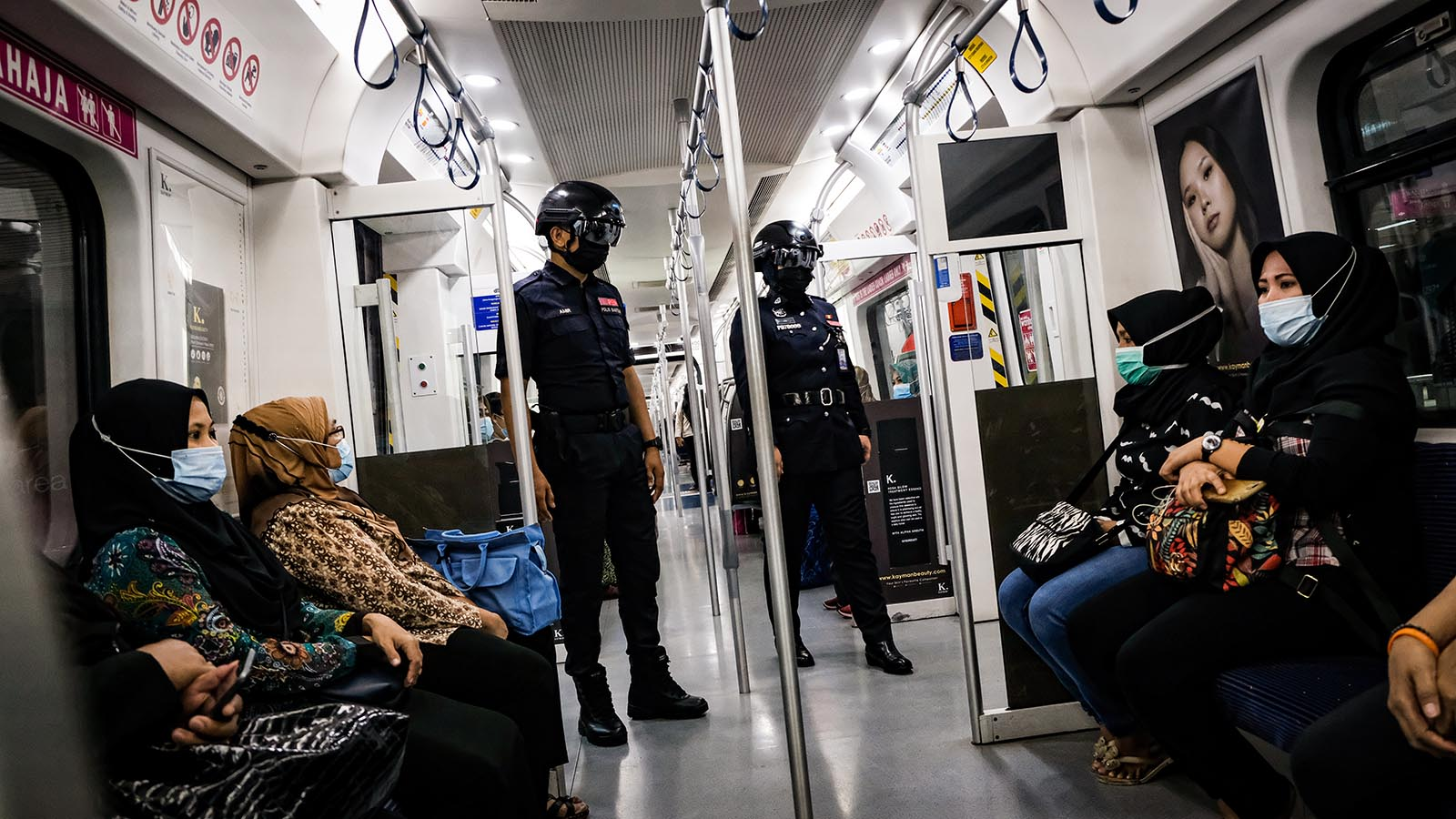 Officers of Keretapi Tanah Melayu Berhad, the main rail line in Malaysia, wear a special helmet that's able to scan the temperature of civilians at KL Sentral, Kuala Lumpur on December 2, 2020.