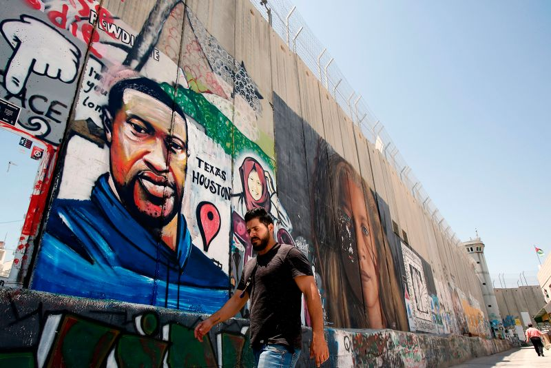 A Palestinian man walks past graffiti of George Floyd in Bethlehem in the occupied West Bank on June 7.