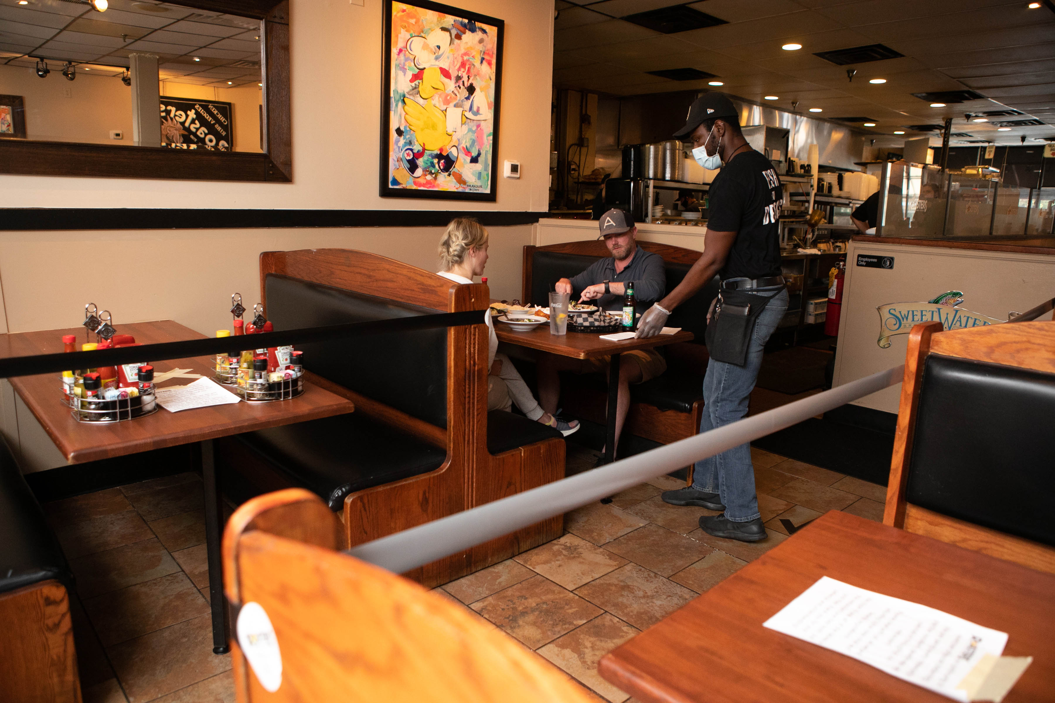 Server Ayite Medji waits on customers Gene and Julia Schatlock on the first day back of dine-in service at Roasters in Atlanta on April 27.