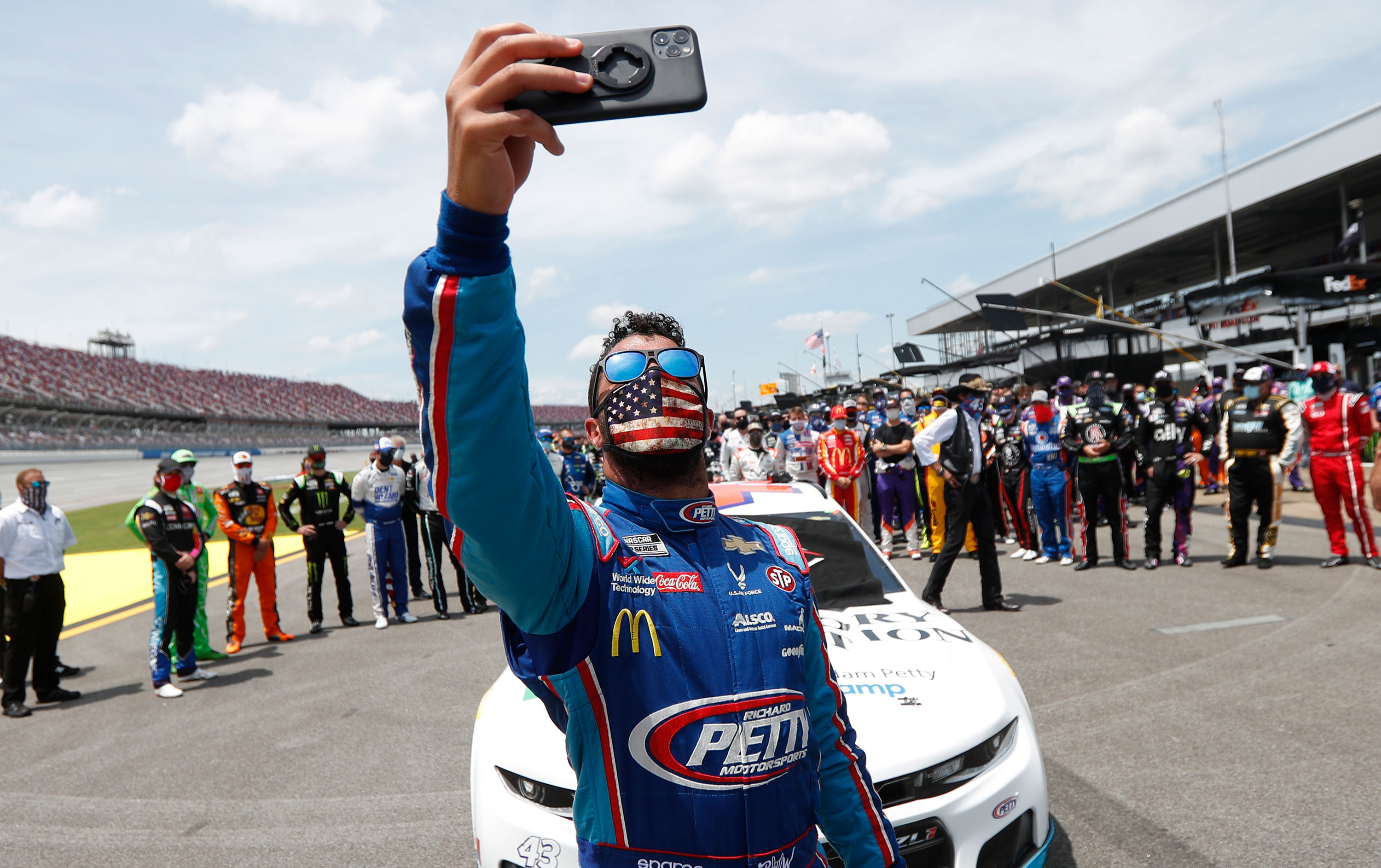 Bubba Wallace takes a selfie of himself and other drivers that pushed his car to the front in the pits of the Talladega Superspeedway prior to the start of the NASCAR Cup Series race on June 22 in Talladega, Alabama.