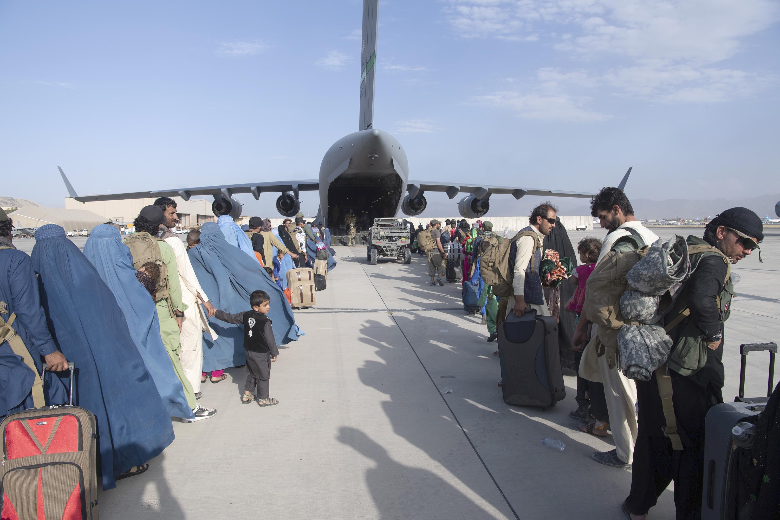 People being evacuated from Afghanistan queue to board an U.S. Air Force C-17 Globemaster III aircraft at Hamid Karzai International Airport on August 24.
