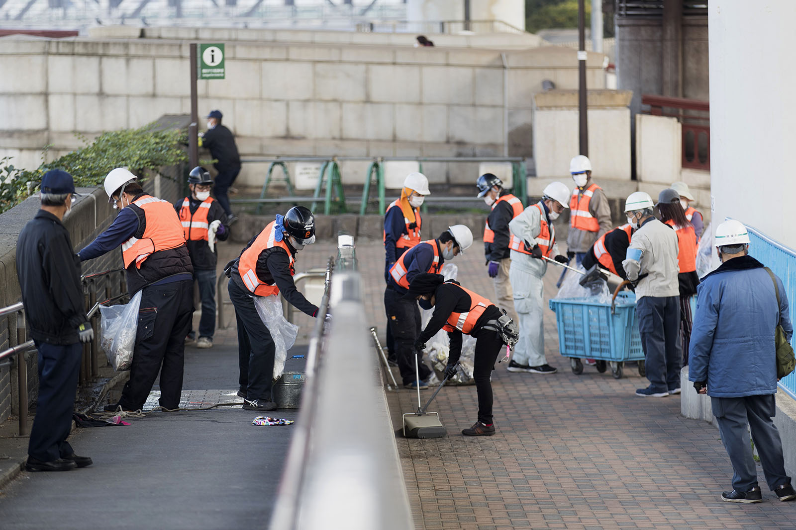 Mask-wearing custodians clean handrails and pick up trash near Sumida River in Tokyo on Friday, December 11.
