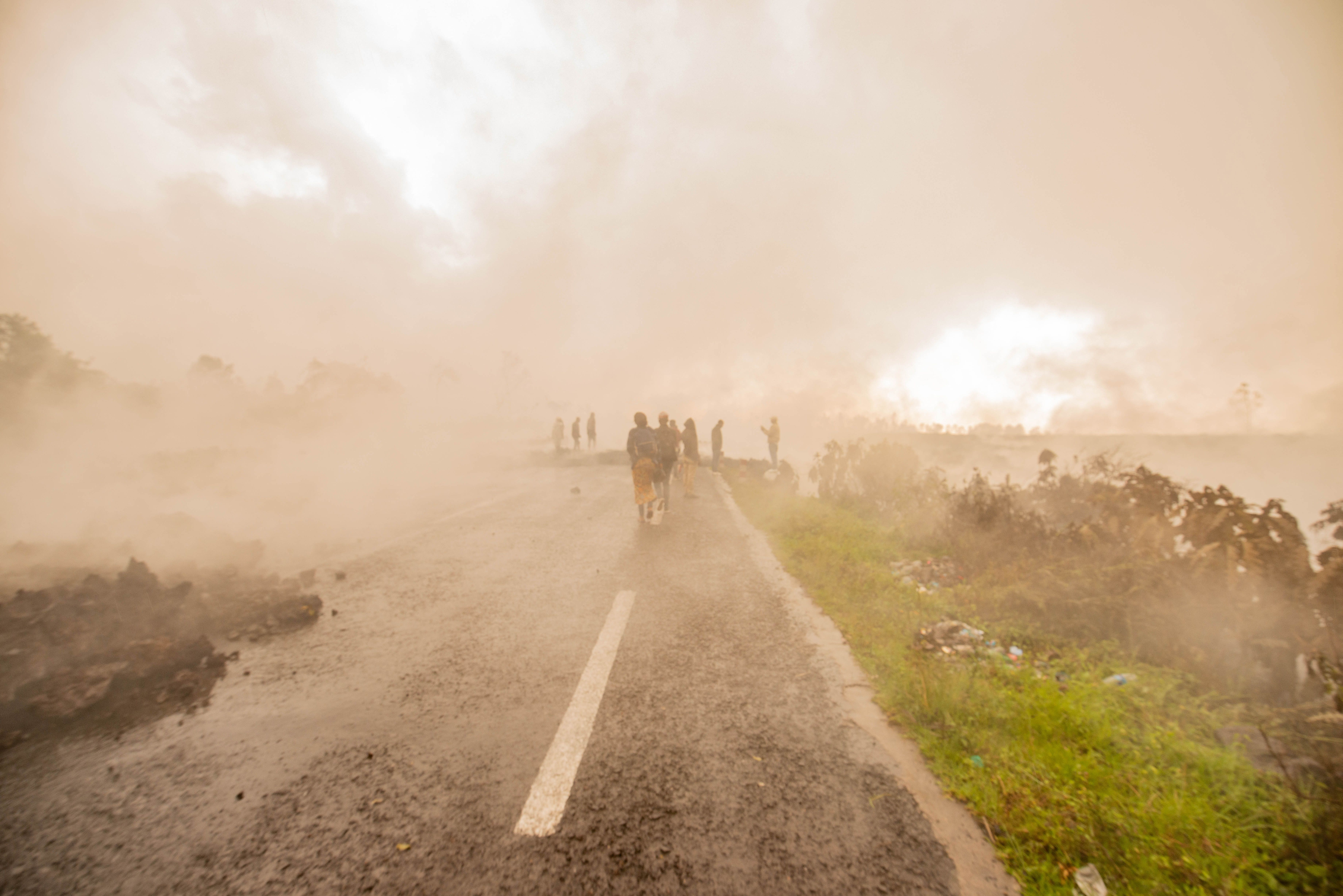 Residents walk through the smoke from smouldering lava flewing from Mount Nyiragongo in Goma on Sunday, May 23