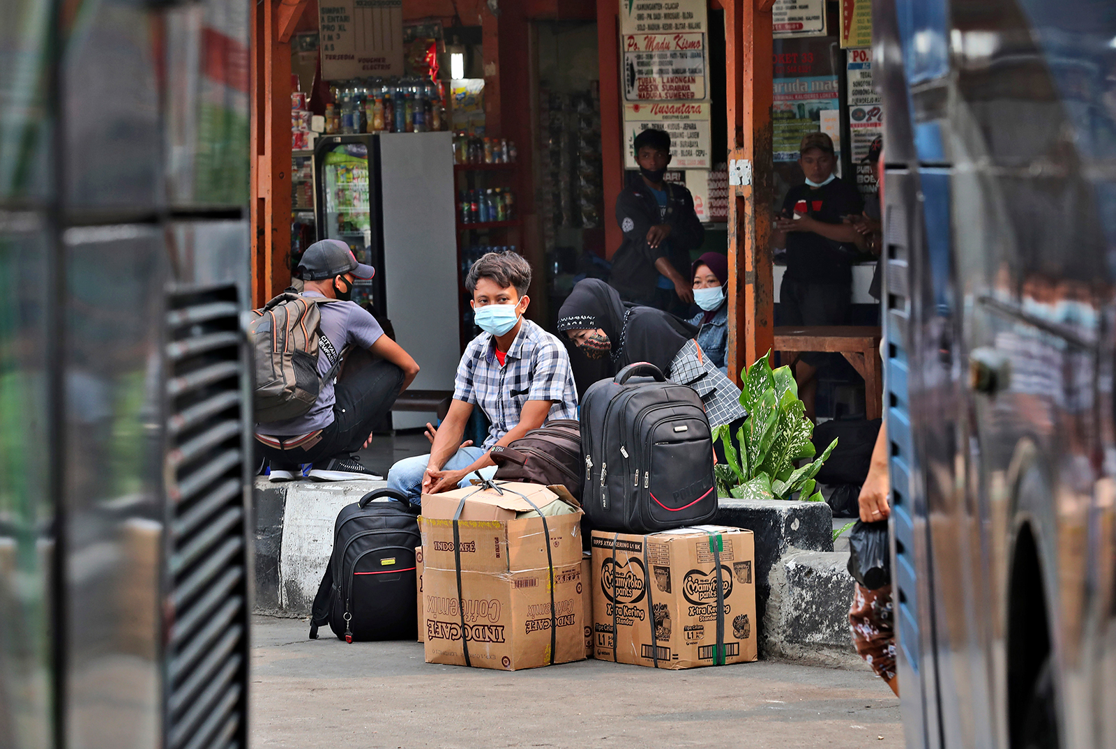 People wait for a bus to take them to their home villages at the Kalideres bus terminal in Jakarta, Indonesia, on May 5.