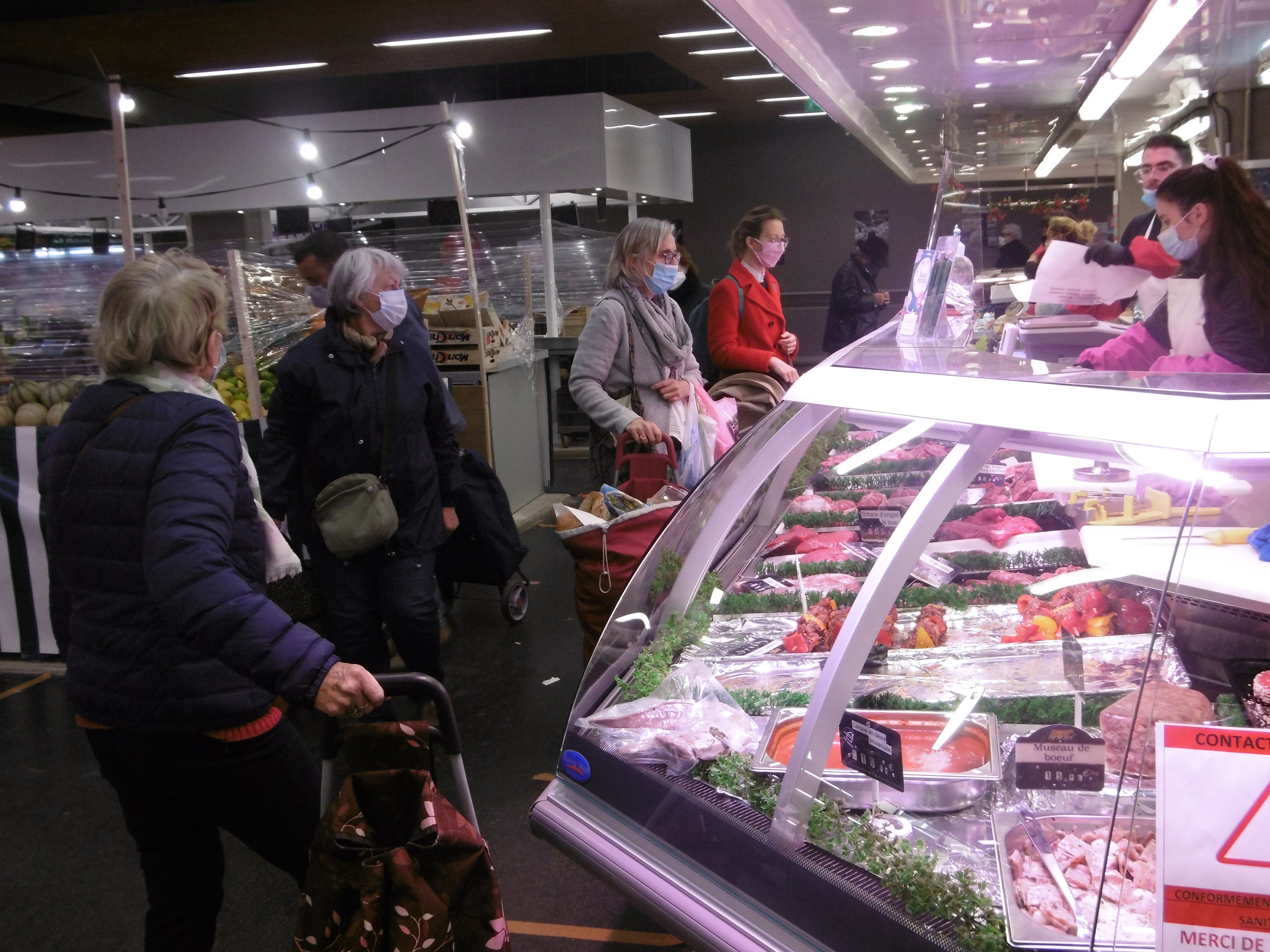 Shoppers stand in line to buy meat from a market in Malakoff, France, on June 17.
