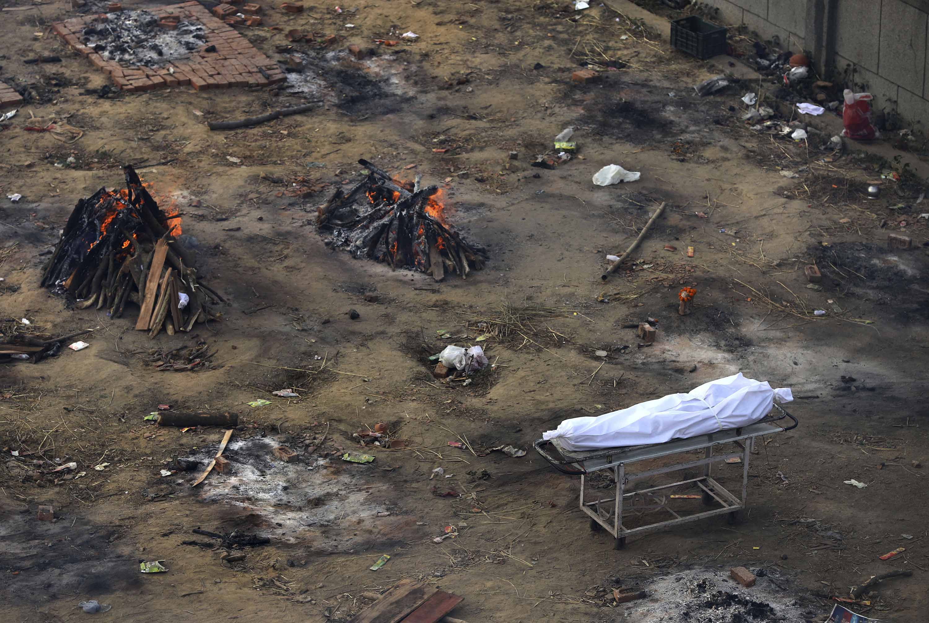 A body waiting for cremation is seen among funeral pyres of Covid-19 victims at a ground that has been converted into a mass crematorium in New Delhi, on April 21.