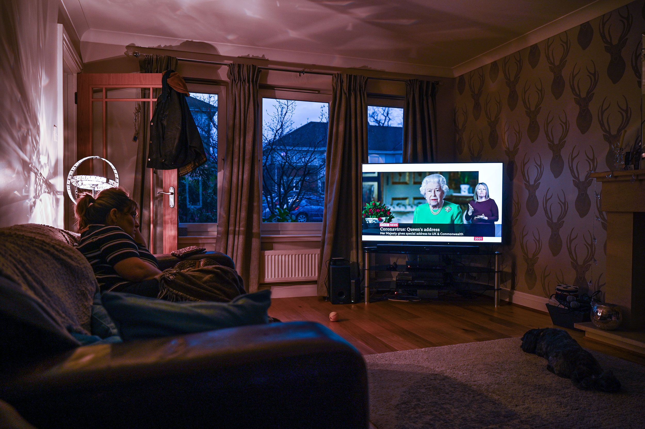 A woman watches Queen Elizabeth II give a televised address on April 5, in Glasgow, Scotland.