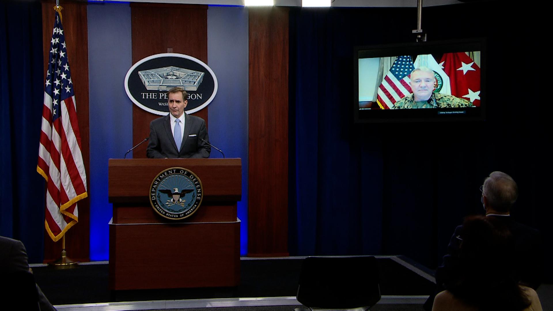 Gen. Frank McKenzie, seen on a TV, and Pentagon press secretary John Kirby.