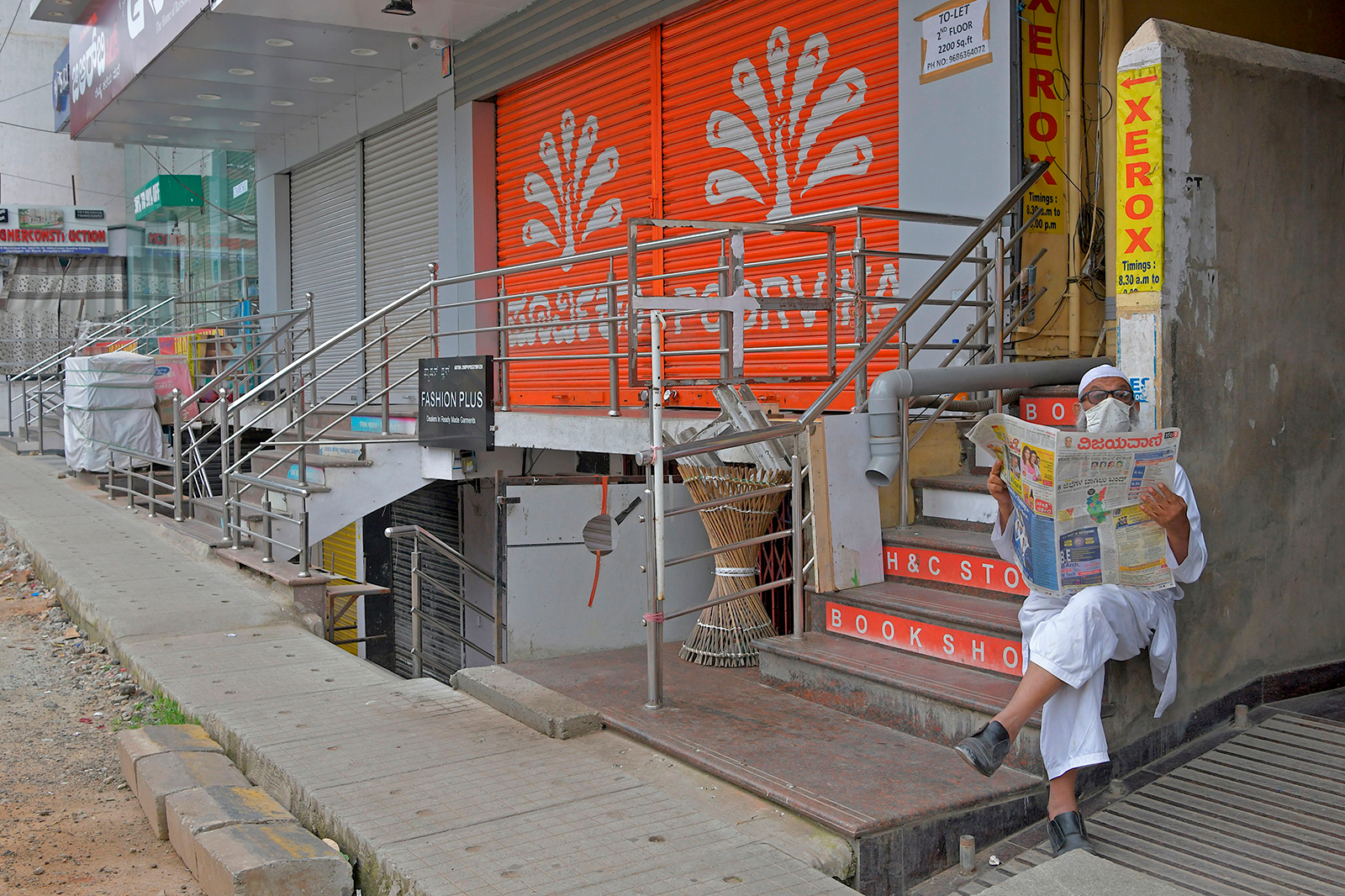 A man reads a newspaper while sitting in front of closed shops in a commercial area in Bangalore, India on July 15.