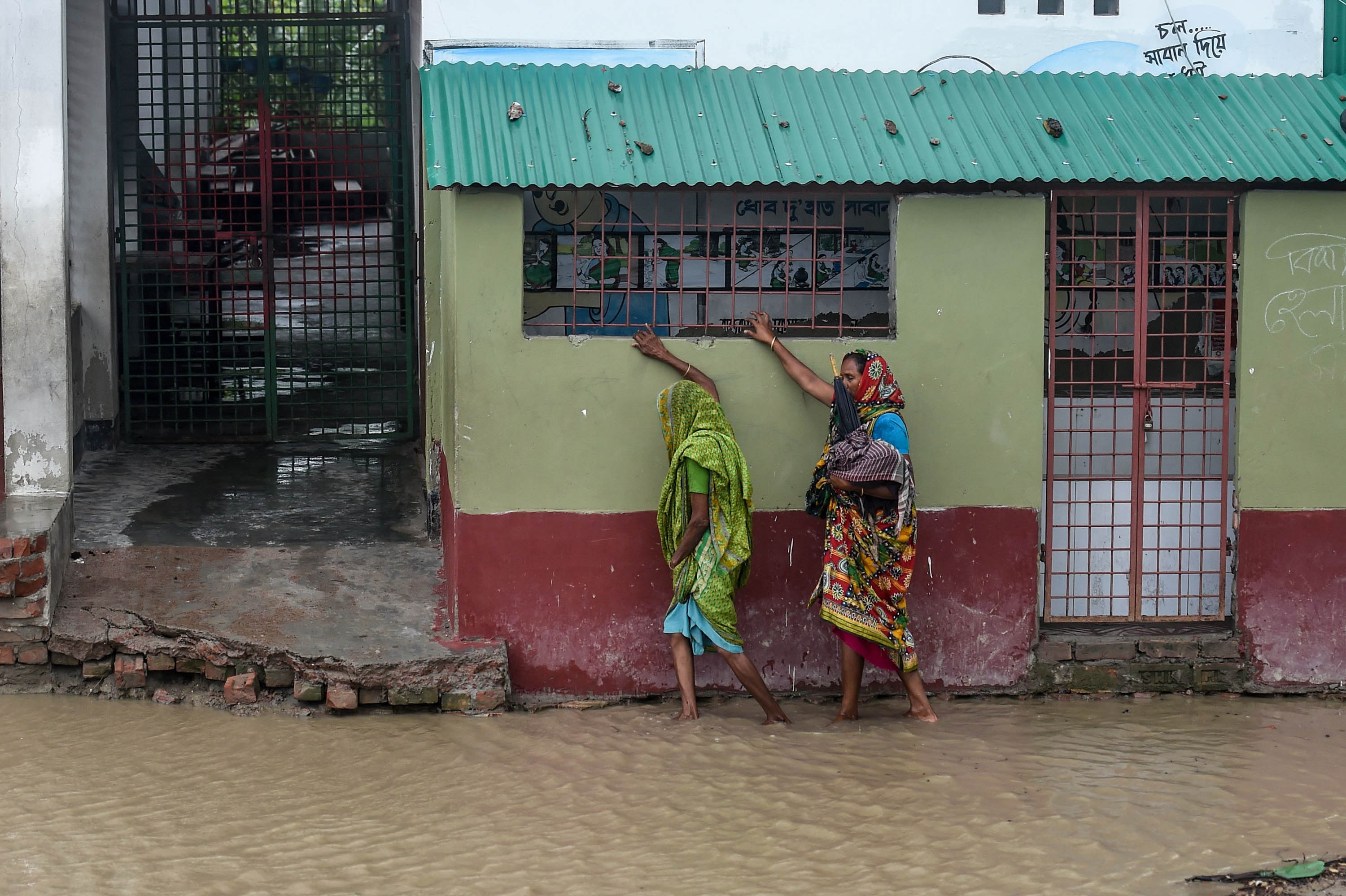 Residents walk along a flooded street in Dacope, Bangladesh, on Wednesday as they head to a shelter before cyclone Amphan made landfall.