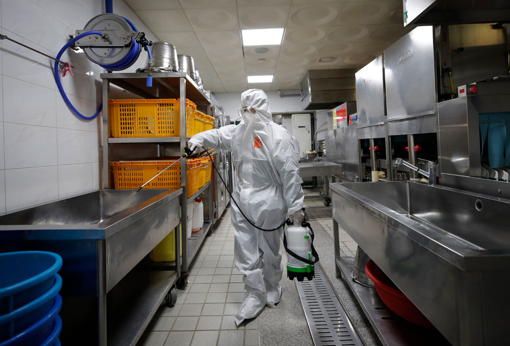 A health official wearing protective gear sprays disinfectant to help reduce the spread the coronavirus ahead of school reopening in a cafeteria at a high school in Seoul, South Korea on Monday, May 11.
