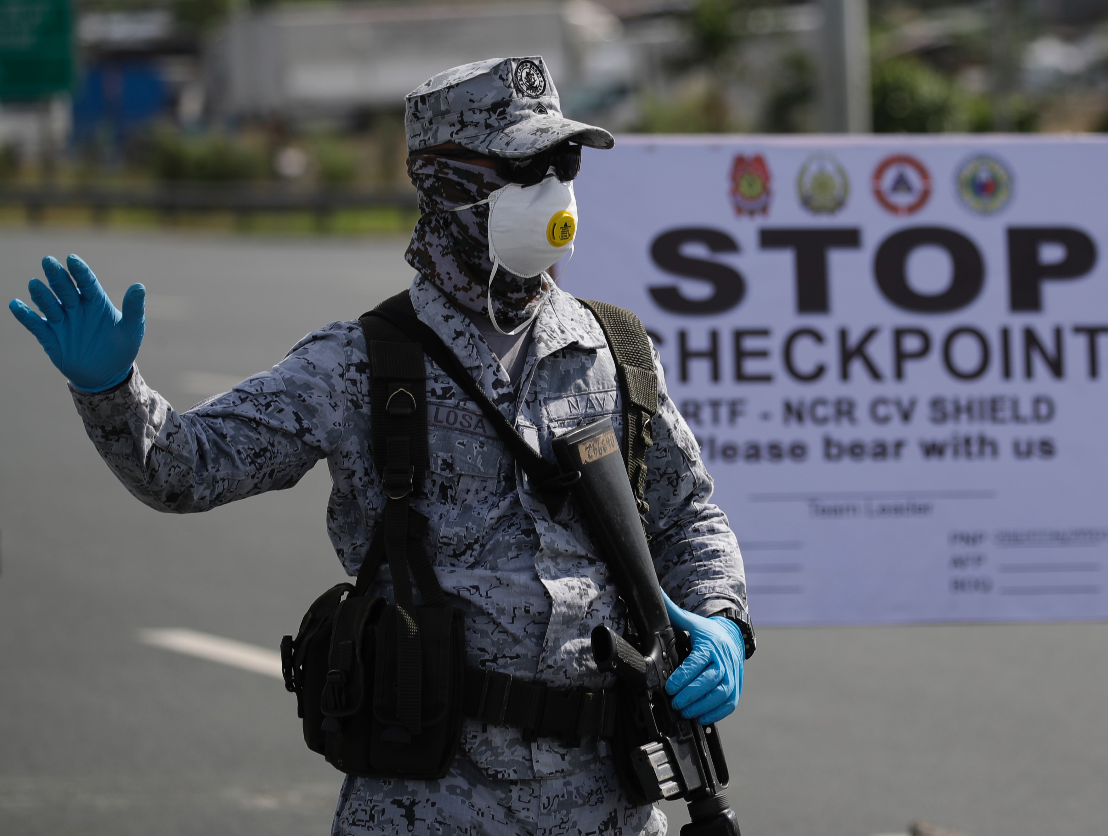 APhilippine Navy serviceman stands at a toll plaza to conduct motorist verification operations on the border between Cavite province and Paranaque City, Metro Manila, Philippines, on March 17.
