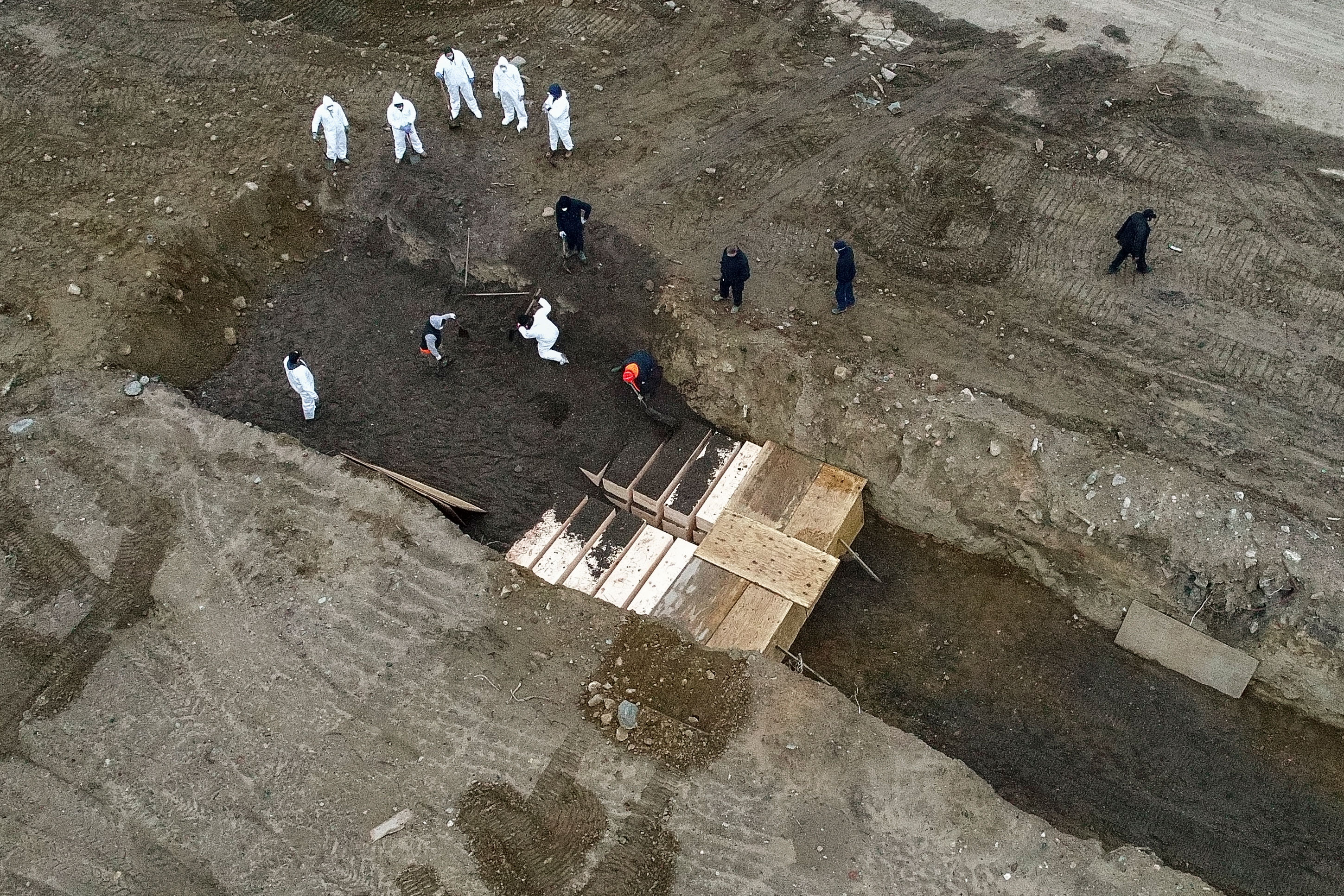 Workers bury bodies on Hart Island, in the Bronx borough of New York, on April 9.