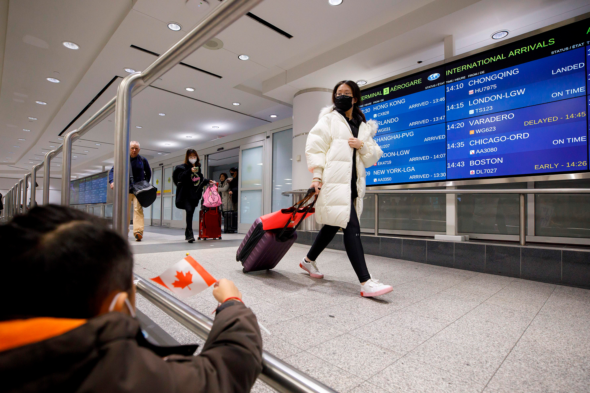 Travelers are seen wearing masks at the international arrivals area at the Toronto Pearson Airport on January 26.