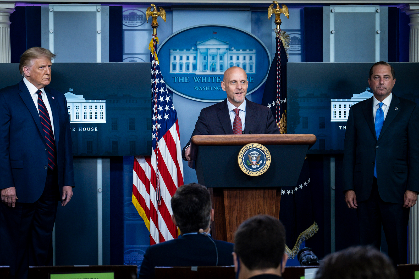 US President Donald Trump and Health and Human Services Secretary, Alex Azar look on as FDA Commissioner Stephen Hahn addresses the media during a press conference in James S. Brady Briefing Room at the White House on on August 23, in Washington, DC.