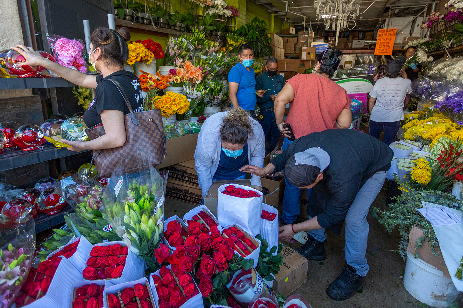 People mingle in close proximity to one another as businesses in the flower district reopen on May 8, 2020 in Los Angeles, California.