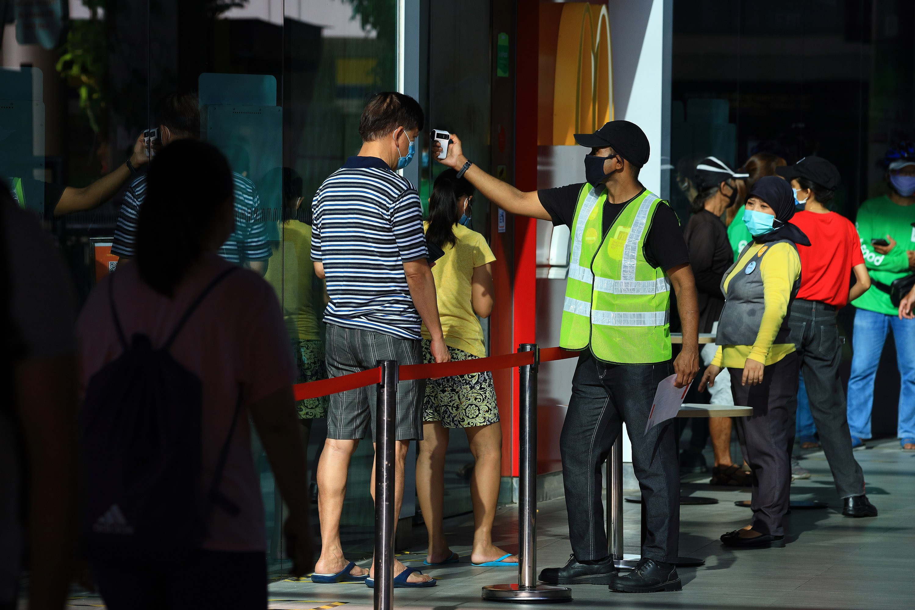 A man wearing a protective mask has his temperature taken before entering a McDonald's restaurant in Singapore, on May 12.