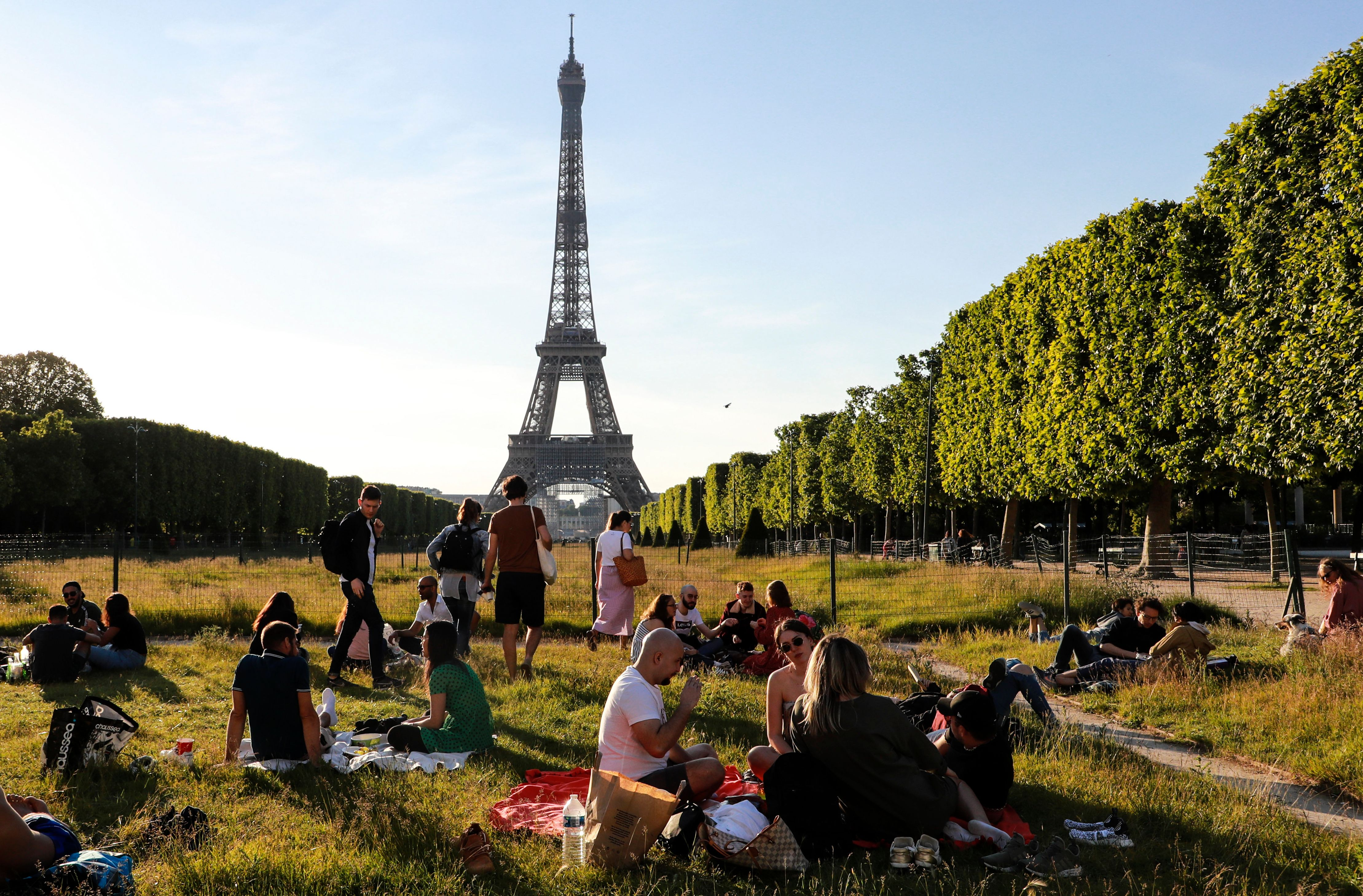 People sit on the Champs de Mars at sunset in front of the Eiffel Tower, on May 17, in Paris.