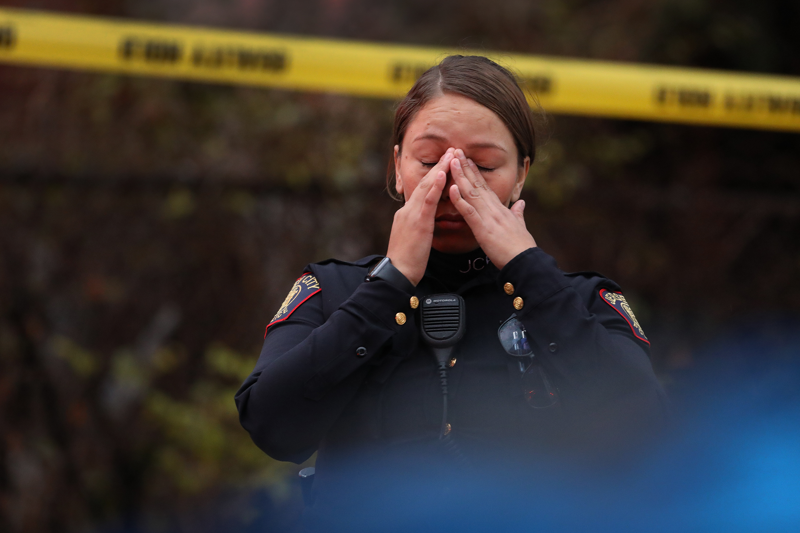 A Jersey City police officer reacts at the scene of a shooting in New Jersey.