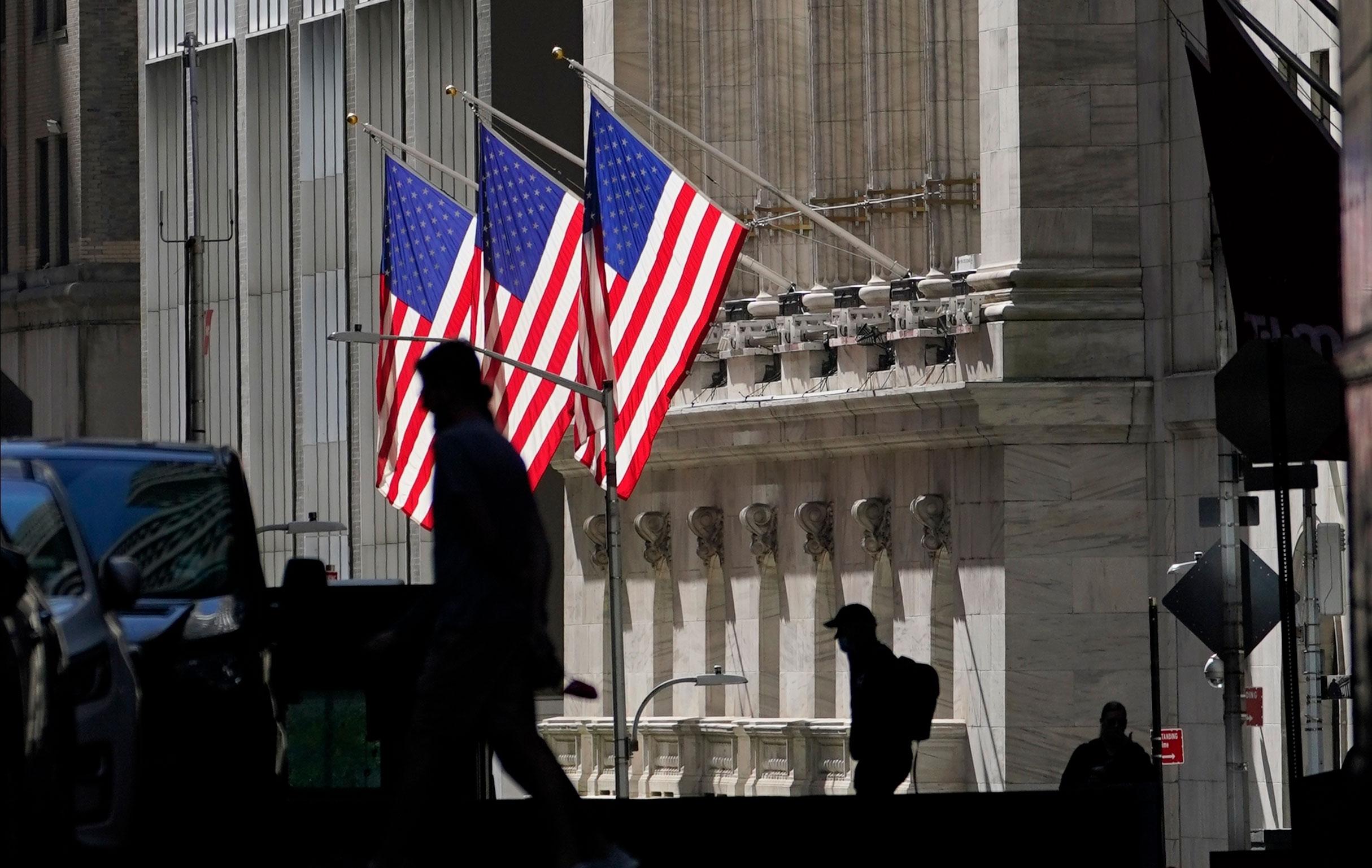 Pedestrians walk past the New York Stock Exchange on October 14.