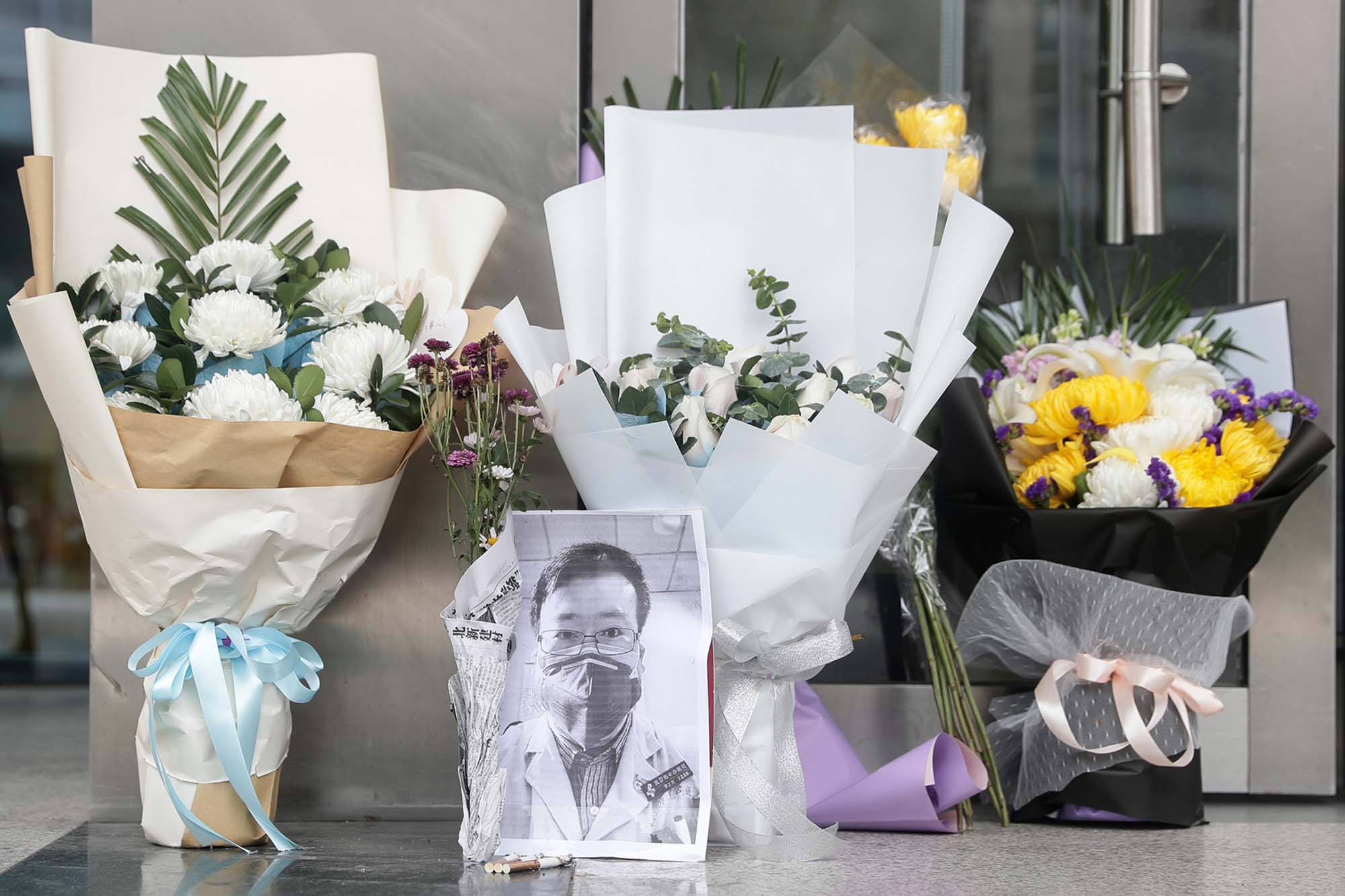 A photo of the late ophthalmologist Li Wenliang is seen beside flower tributes at the Wuhan Central Hospital on Friday.