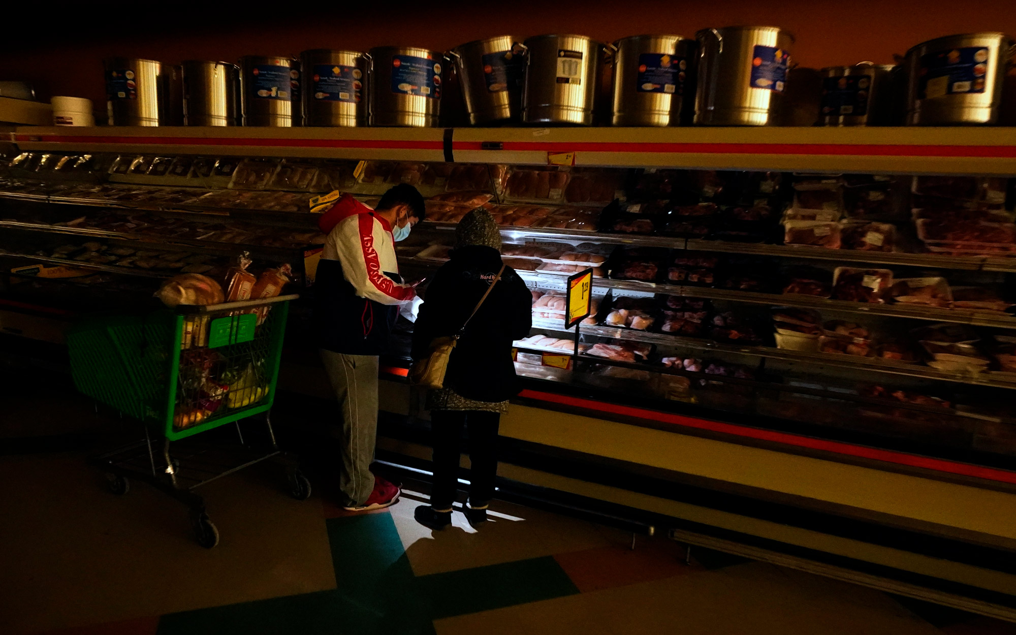 Customers use the light from a cell phone to look in the meat section of a grocery store on February 16 in Dallas, Texas.