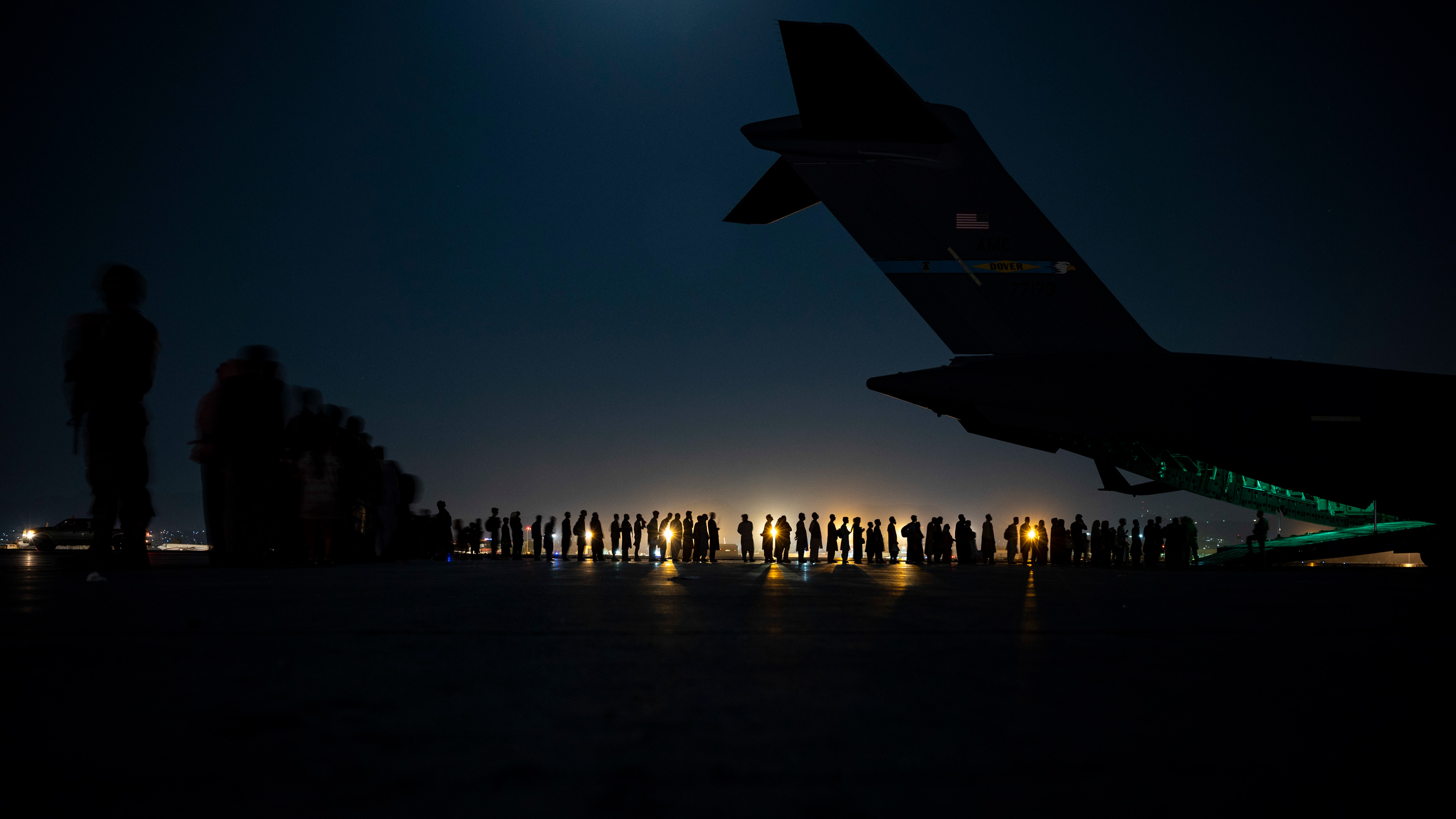 An air crew prepares to load evacuees aboard an aircraft in support of the Afghanistan evacuation at Hamid Karzai International Airport on August 21 in Kabul, Afghanistan.