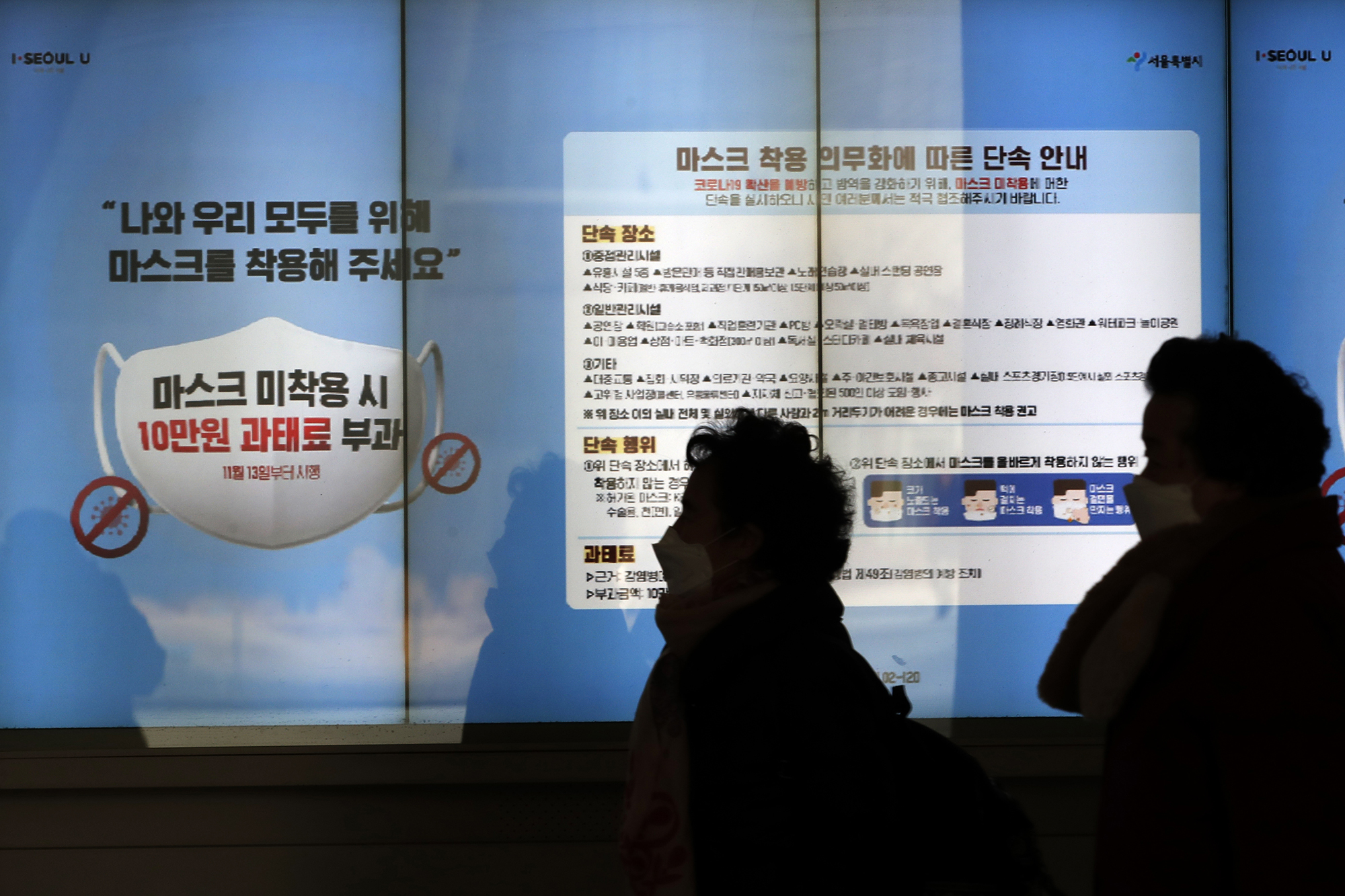 People wearing face masks walk near a screen displaying precautions against the coronavirus in Seoul, South Korea, on Sunday, December 27, 2020.