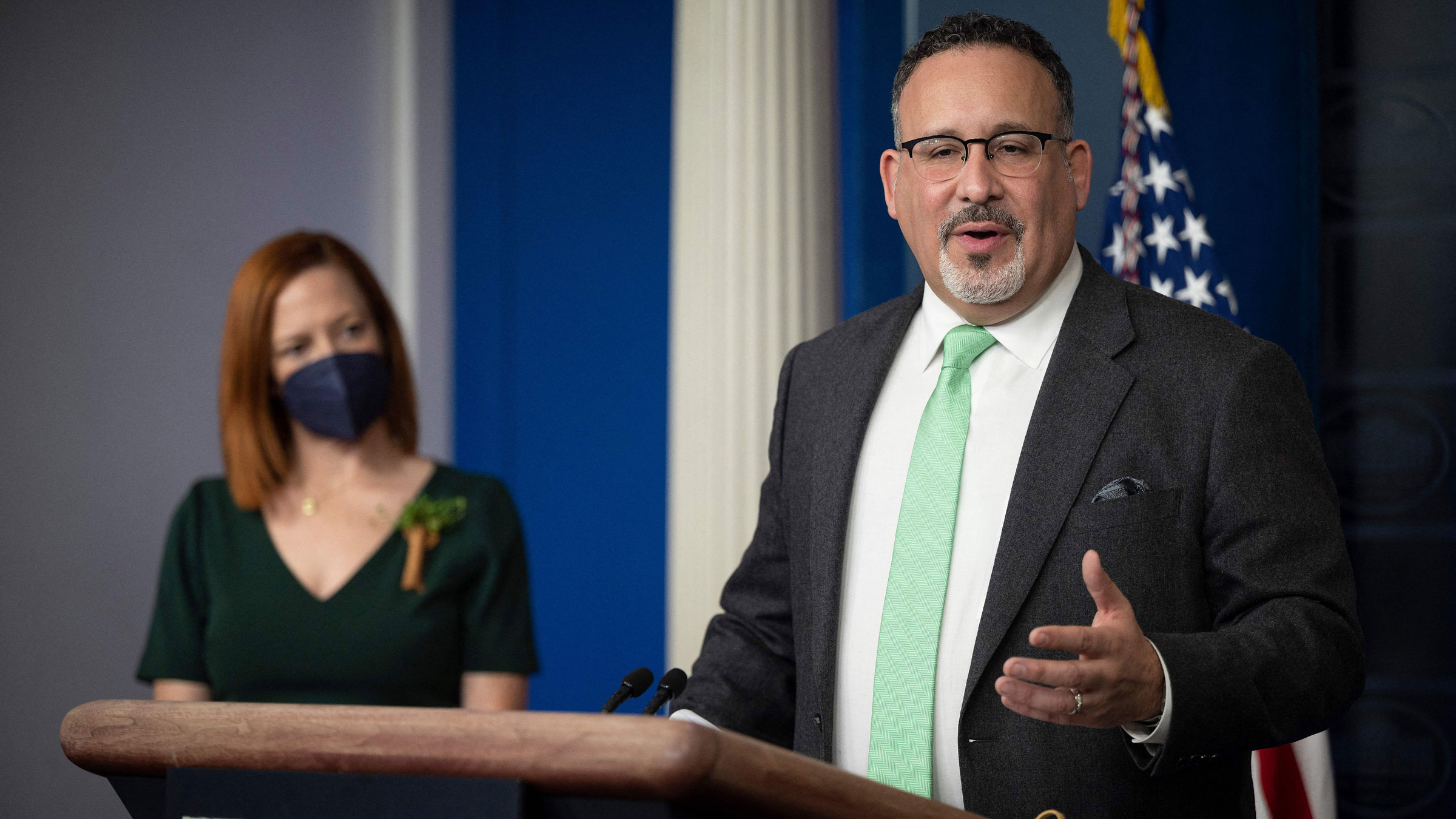 Education Secretary Miguel Cardona, flanked by White House press secretary Jen Psaki, speaks during the daily press briefing at the White House on Wednesday.